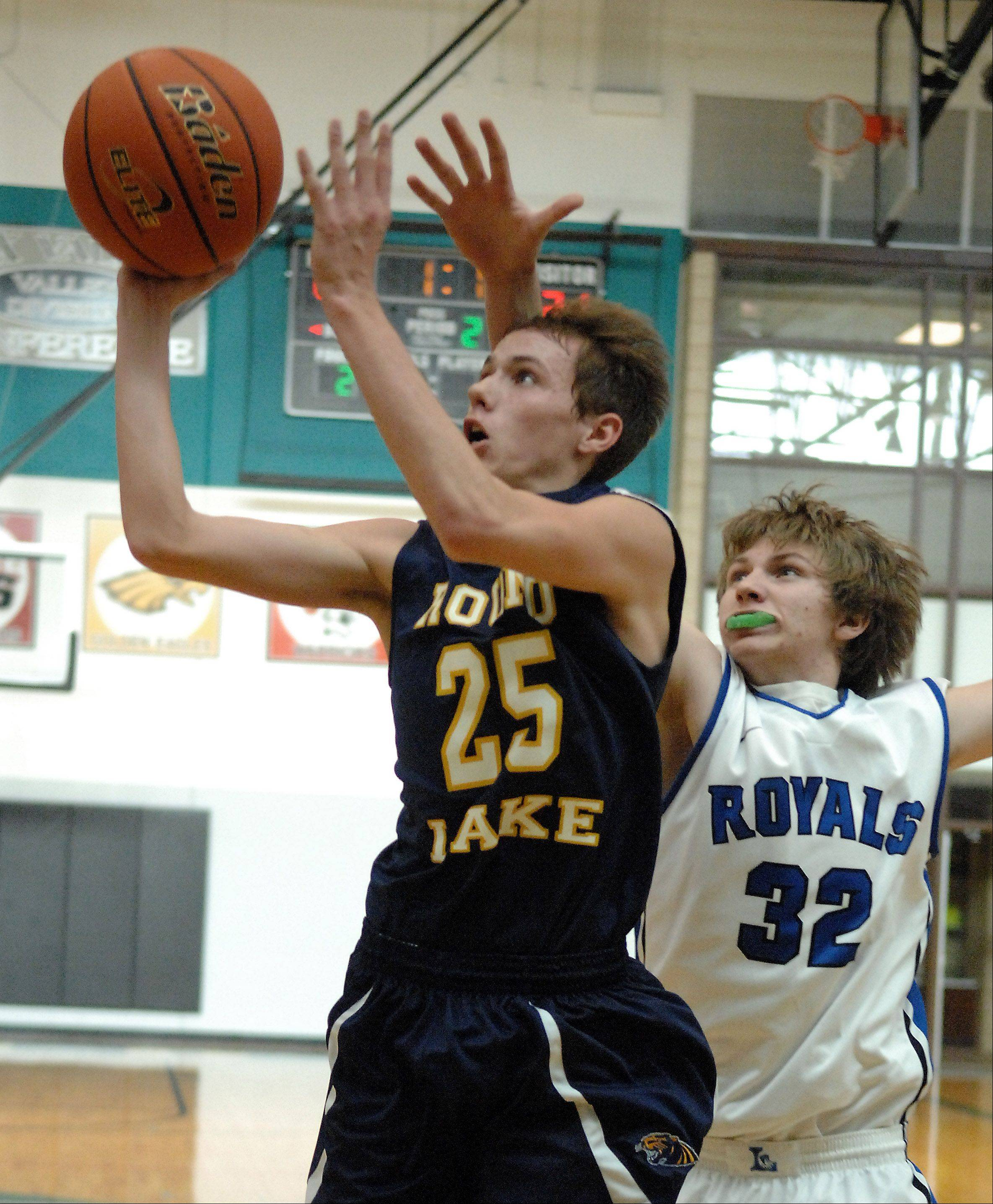 Round Lake's Robert Pisarski scores and is fouled by Larkin's Tanner Gardon (32) during Friday's game at Woodstock North High School.