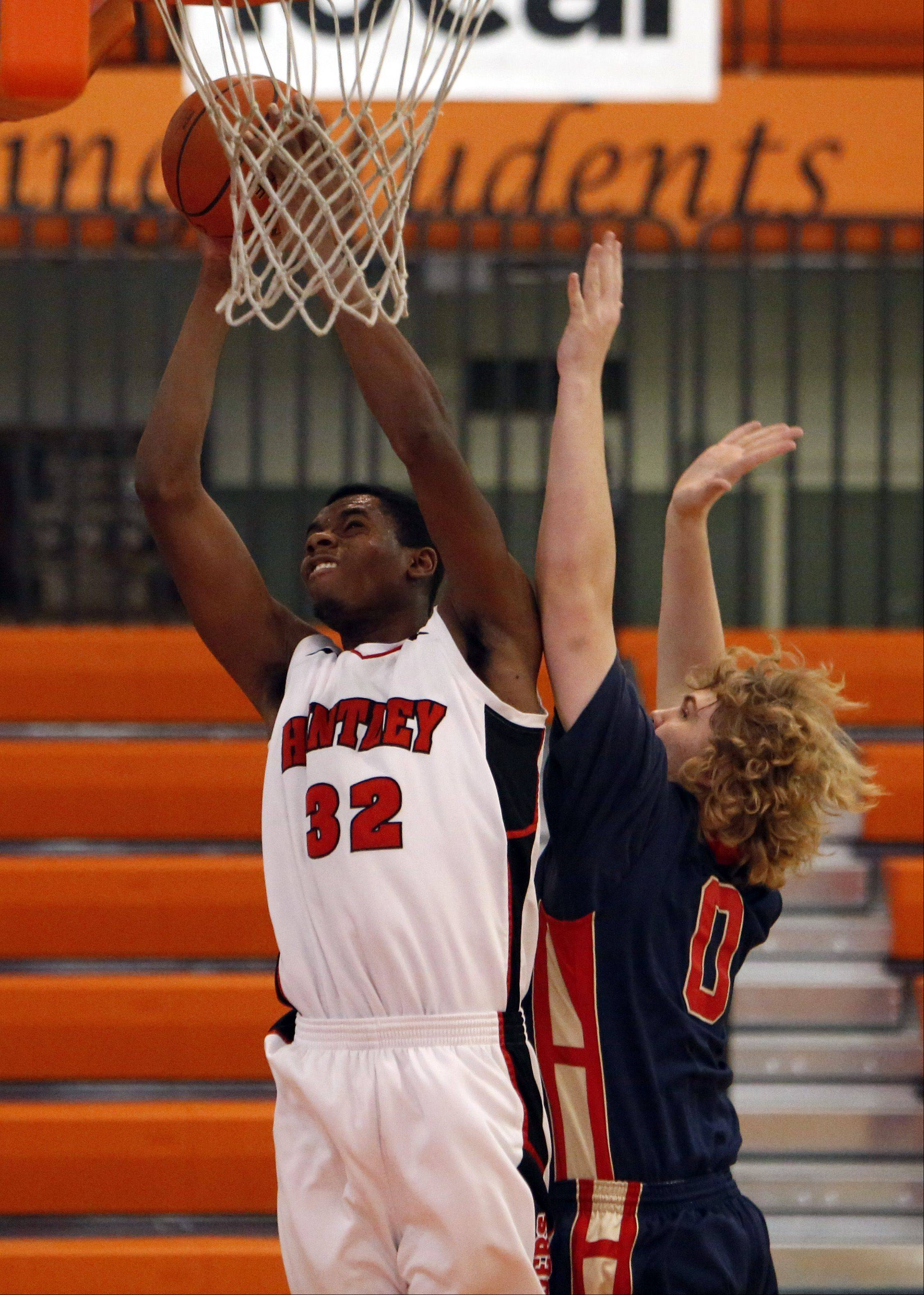 Huntley' s Amanze Egekeze (32) goes strong to the hoop as he is fouled by Belvidere North's Cristopher Meyers during the Crystal Lake Central High School Coaches vs. Cancer Thanksgiving Tourney Saturday in Crystal Lake.