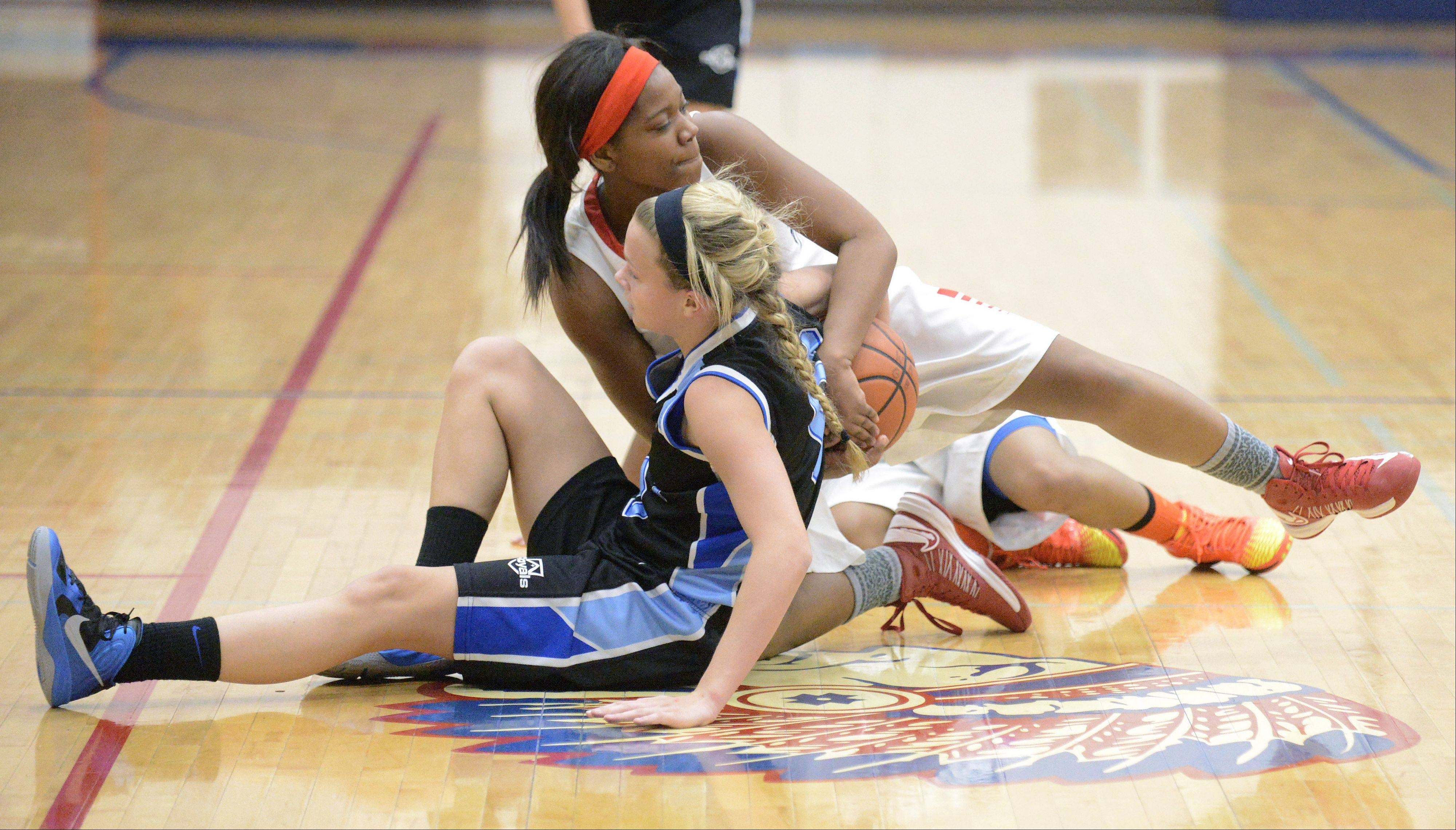 Rosary's Quincy Kellett and West Aurora's Ashley Williams wrestle for a loose ball in the second quarter on Tuesday, December 3.