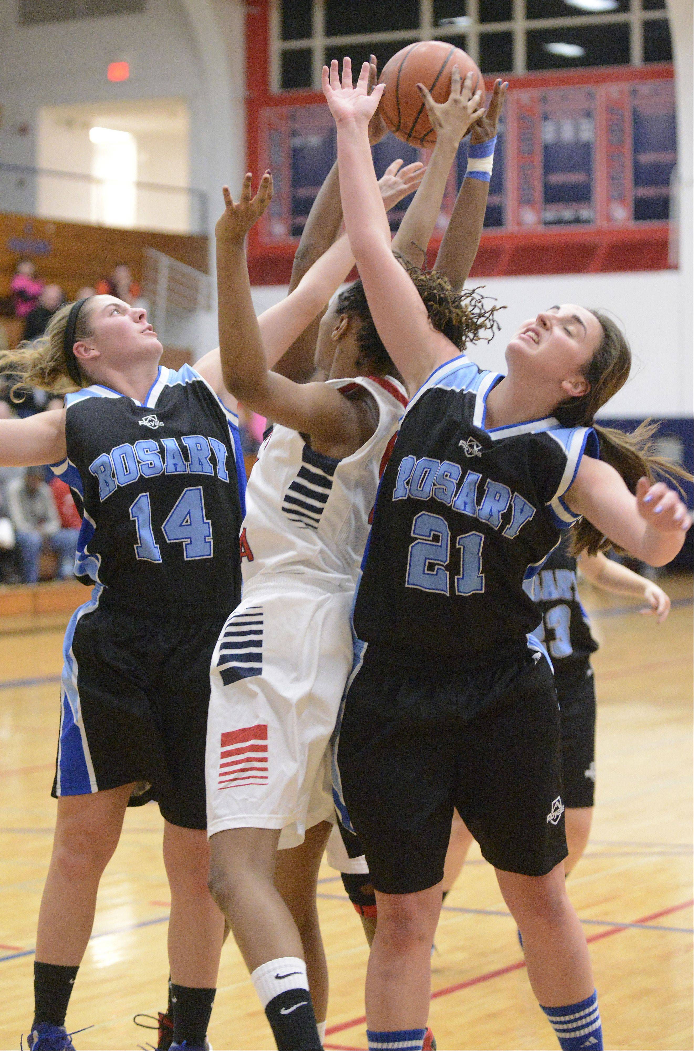 Rosary's Megan Conlin and Adrienne Winkel surround West Aurora's Natalee DeJohnette as they all reach for a Royals rebound in the second quarter on Tuesday, December 3.