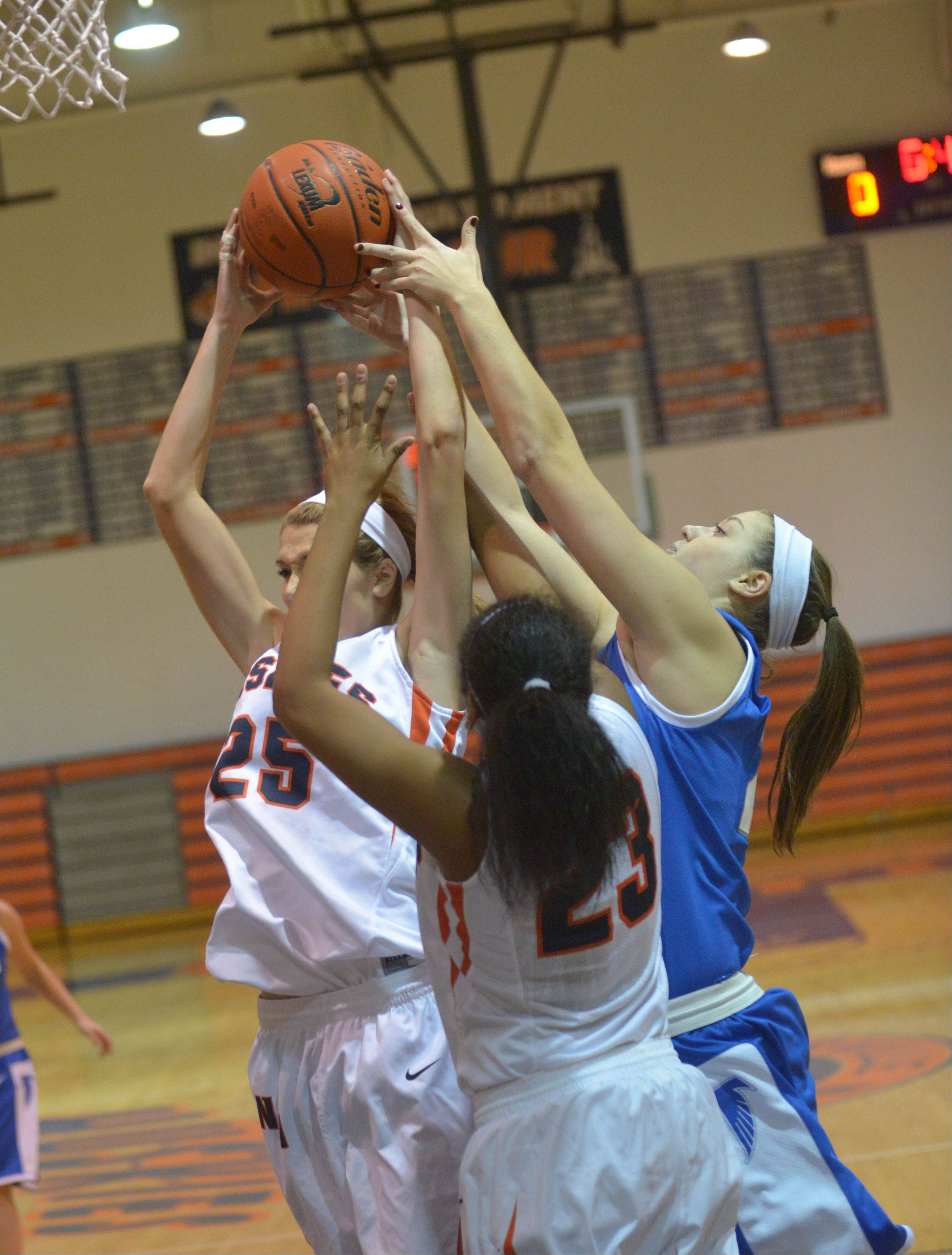 Kayla Sharples of Napervile North,left, and Chrissy Baird of Wheaton North go for a rebound.