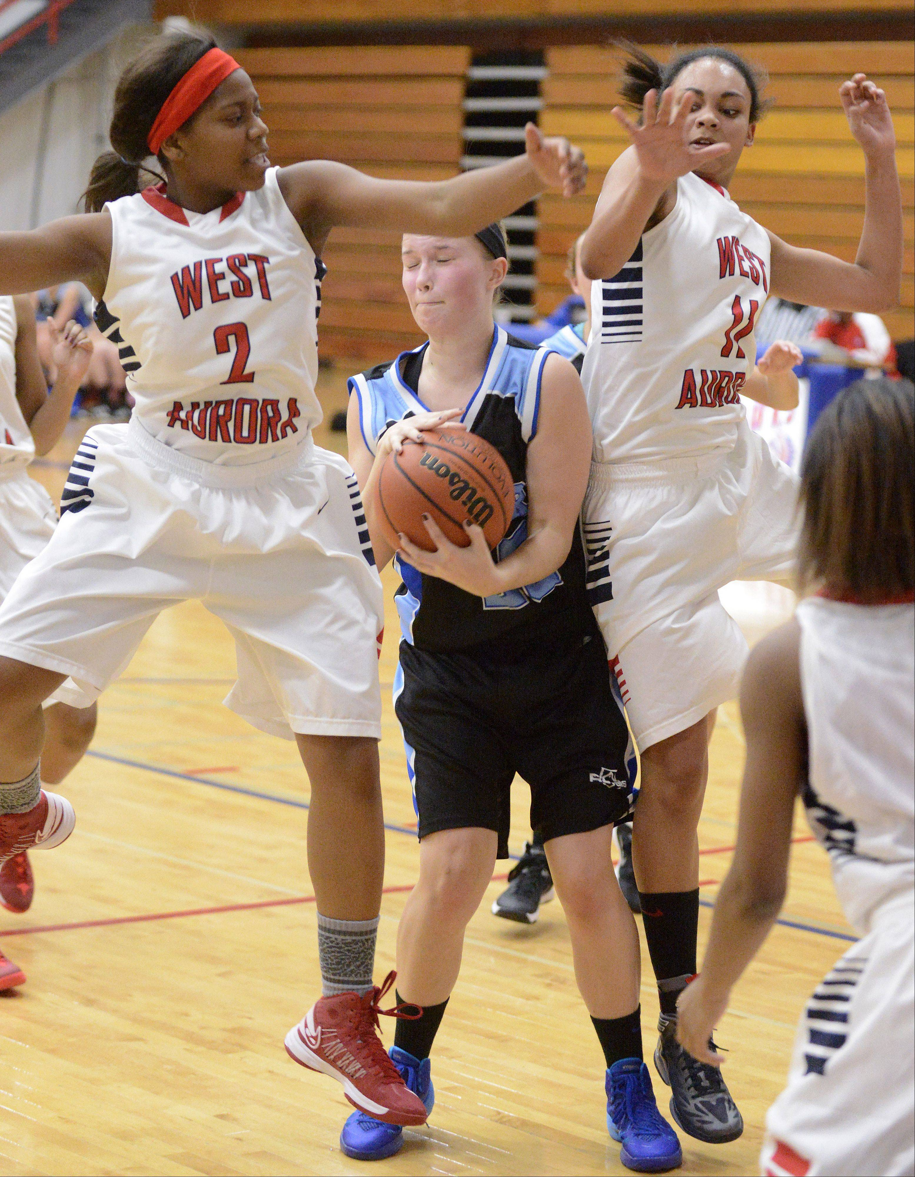 Rosary's Taylor Drozdowski is swarmed by West Aurora's Ashley Williams and Abriya Zeitz.