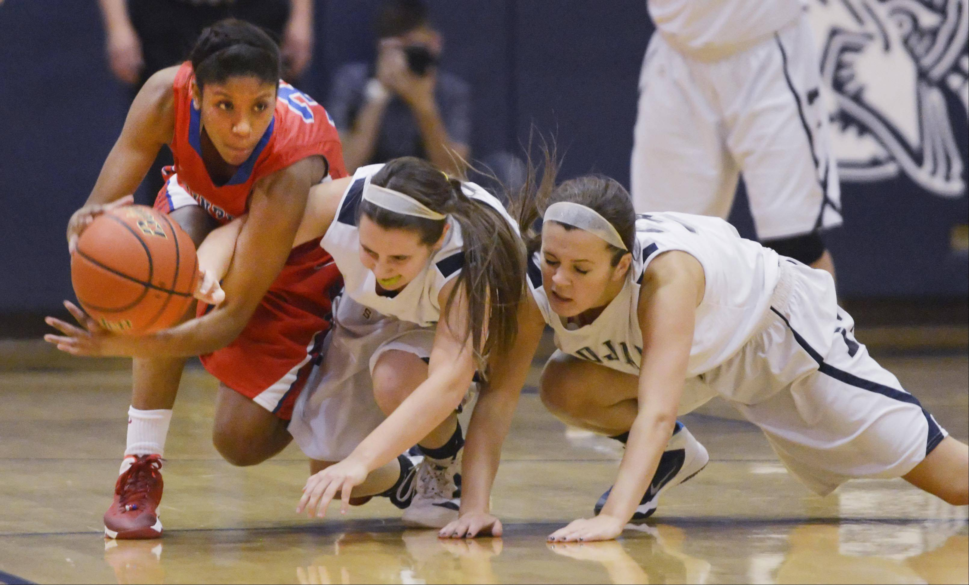 Dundee-Crown's Kayla Lawernce and Cary-Grove's Amy Clemment and Chrissy Sopchyk fight for a loose ball.