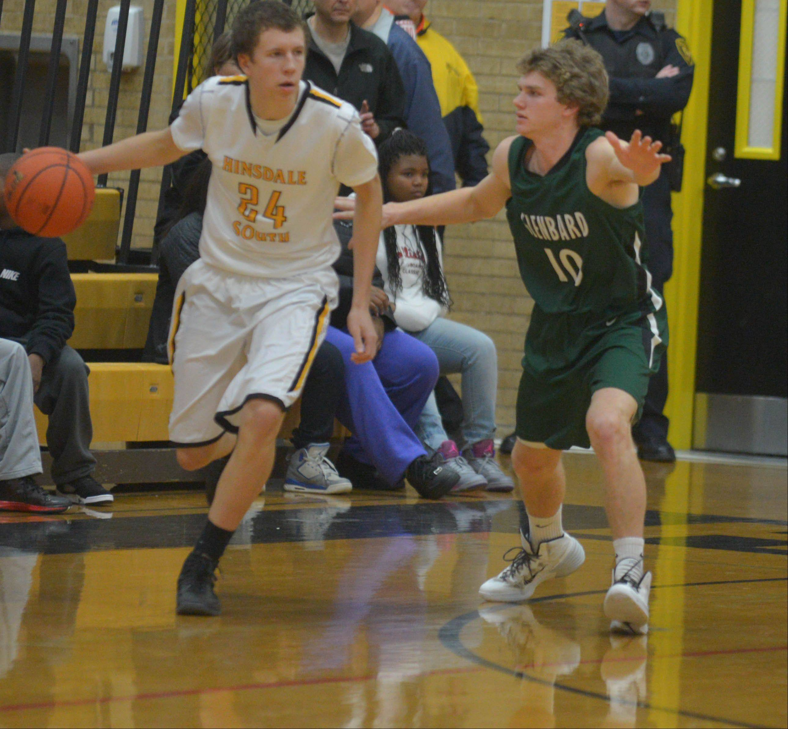 Laurynas Motuzis,left, of Hinsdale South,moves the ball while Max Montgomery of Glenbard West blocks during the Glenbard West at Hinsdale South boys basketball game Wednesday.
