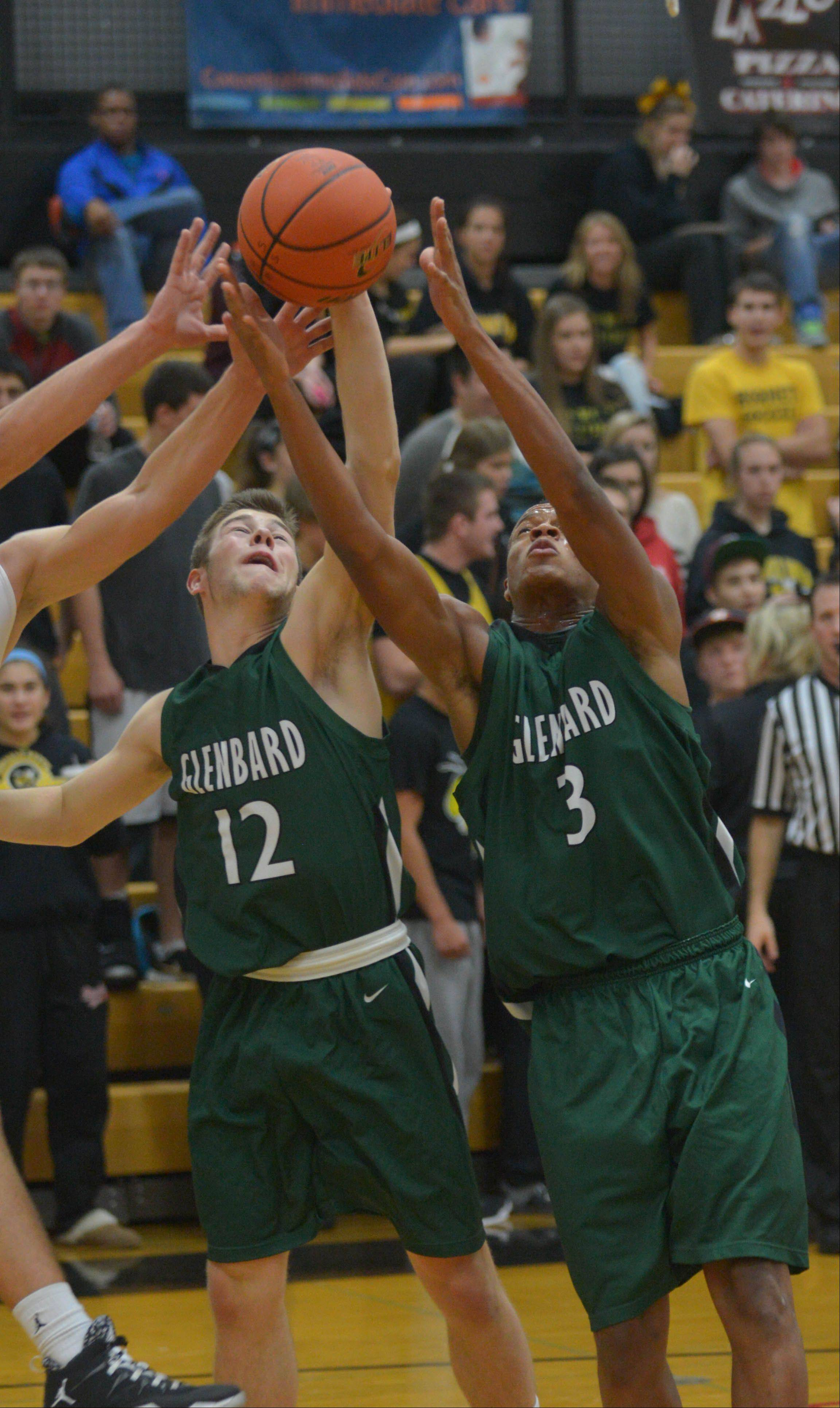 Will Reedy,left, and Kalen Starkey of Glenbard West go for a rebound during the Glenbard West at Hinsdale South boys basketball game Wednesday.