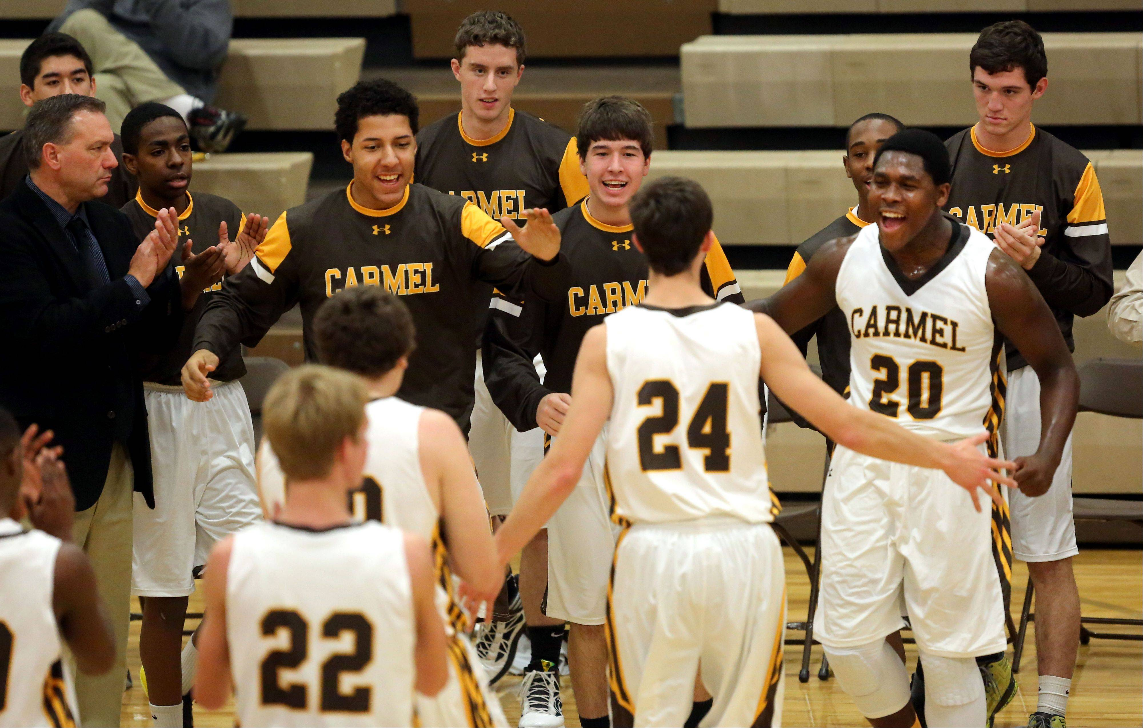 The Carmel bench celebrates after a timeout against Vernon Hills on Wednesday night at Carmel Catholic.