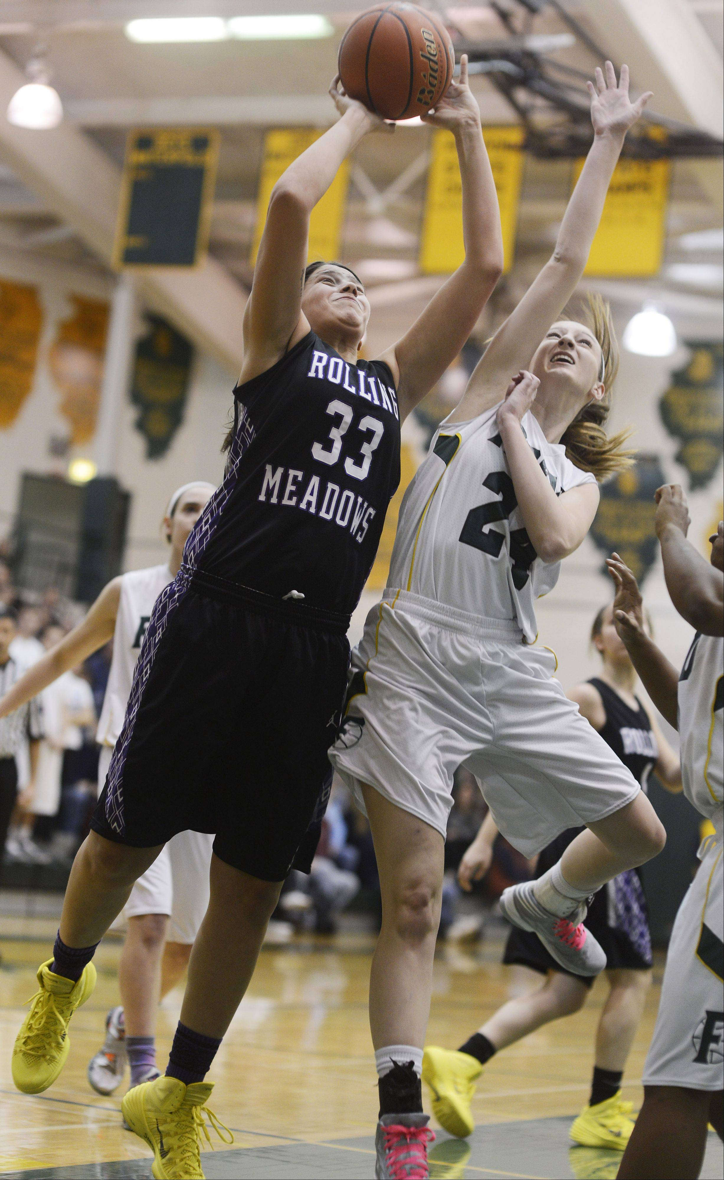 Rolling Meadows' Ashley Montanez, left, makes a strong move to the basket as Fremd's Hanna Labarge tries to block the shot.