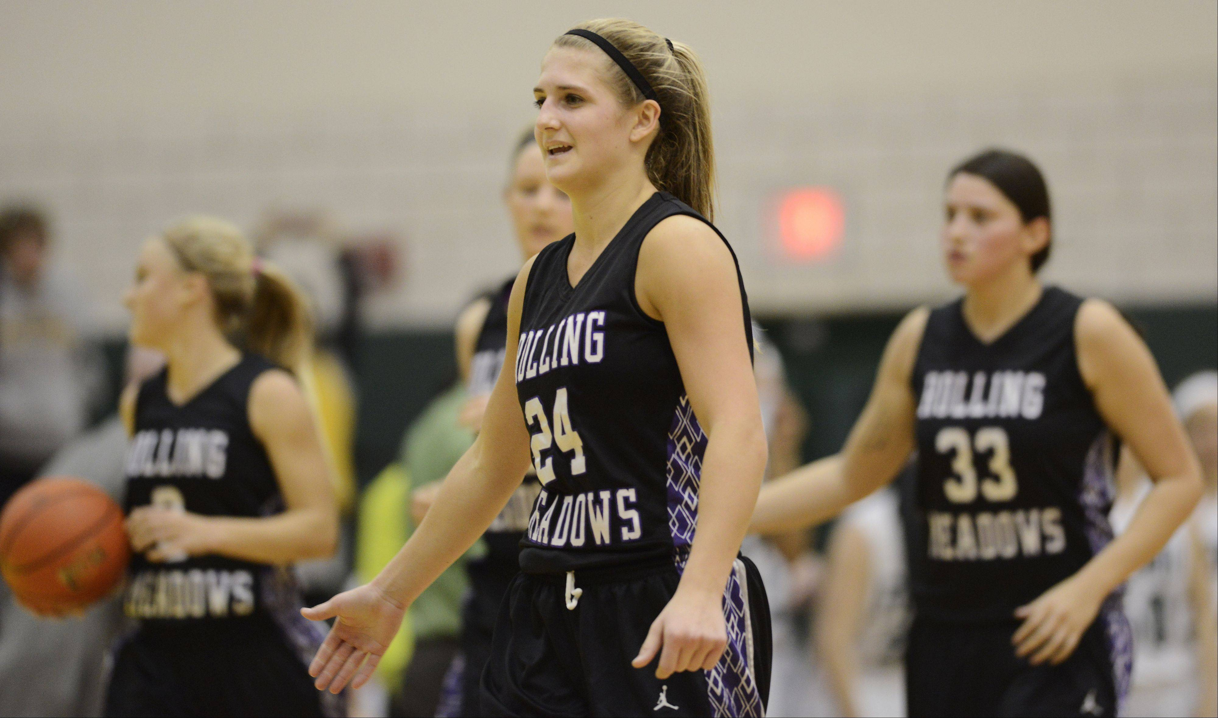 Rolling Meadows' Alexis Glasgow walks off the court with her teammates after a close victory over Fremd.