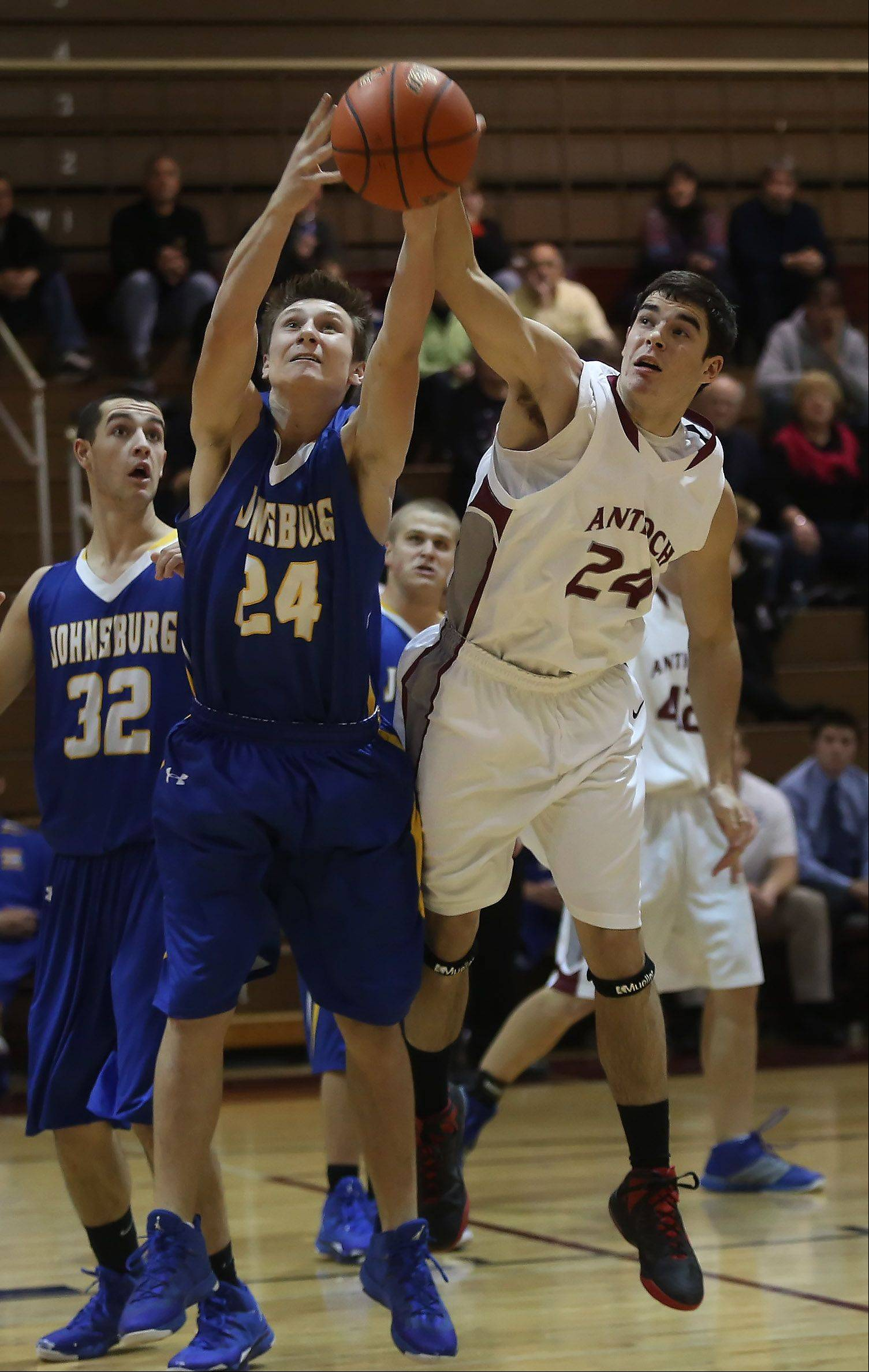 Antioch forward Kyle Gofron battles Johnsburg forward Alec Graef for the rebound during Thursday's game at Antioch.