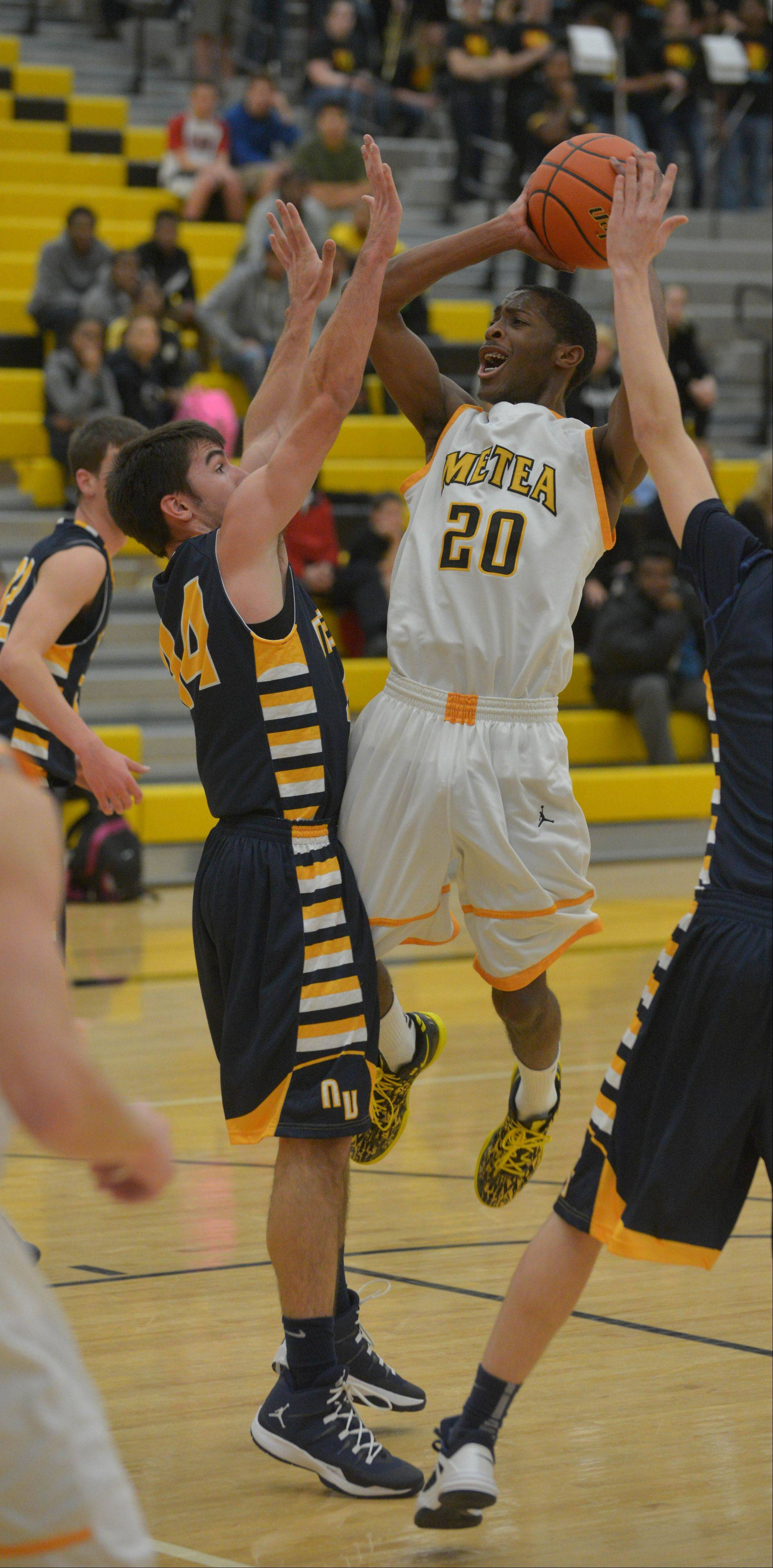 Marquell Oliver of Metea Valley takes a shot while Josh Piotrowski of NeuquaValley during the Neuqua Valley at Metea Valley boys basketball game Thursday.
