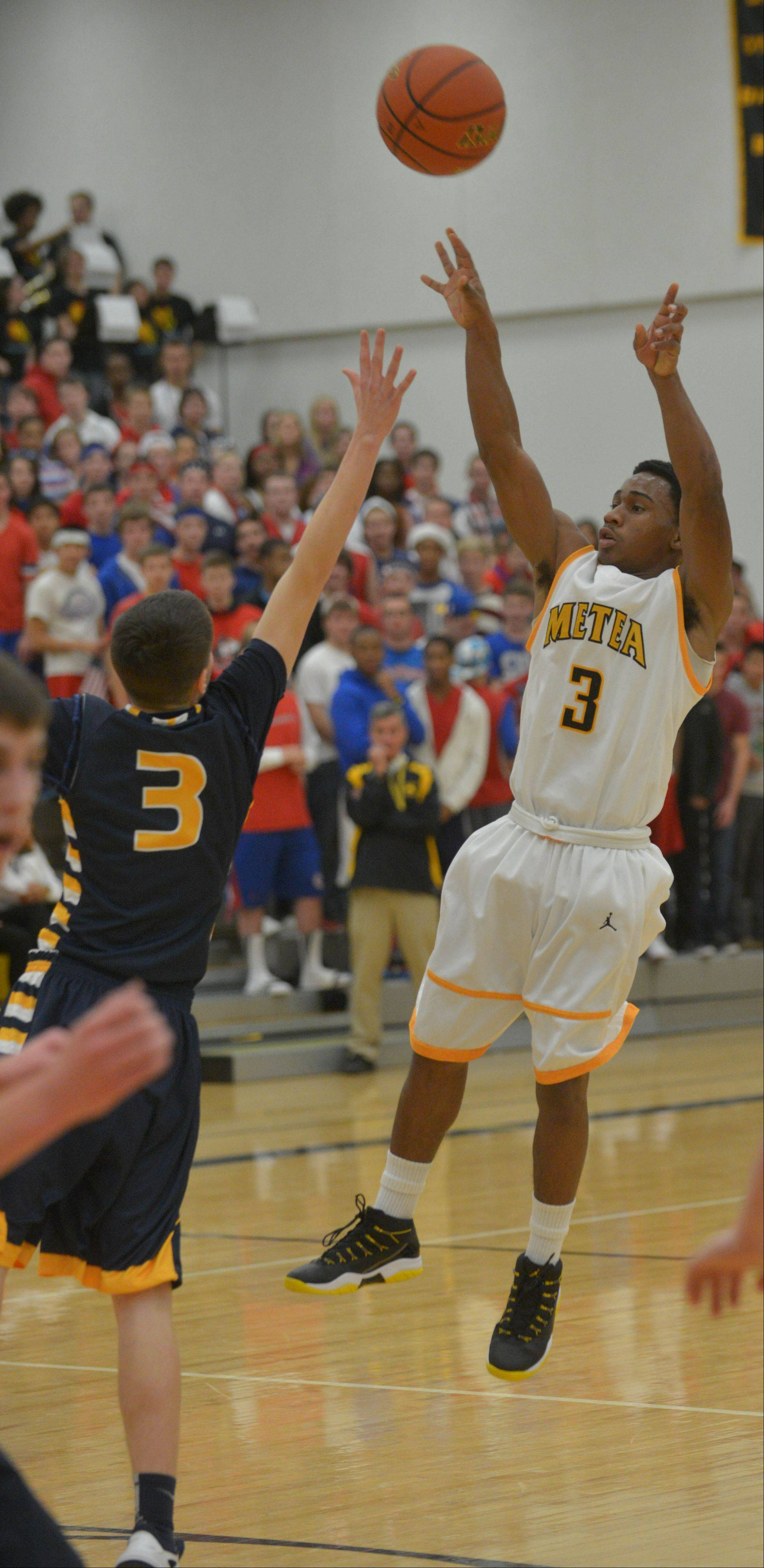 Jordan Kedrowski of Neuqua Valley,left, attempts to block a shot from Bryson Oliver of Metea Valley during the Neuqua Valley at Metea Valley boys basketball game Thursday.