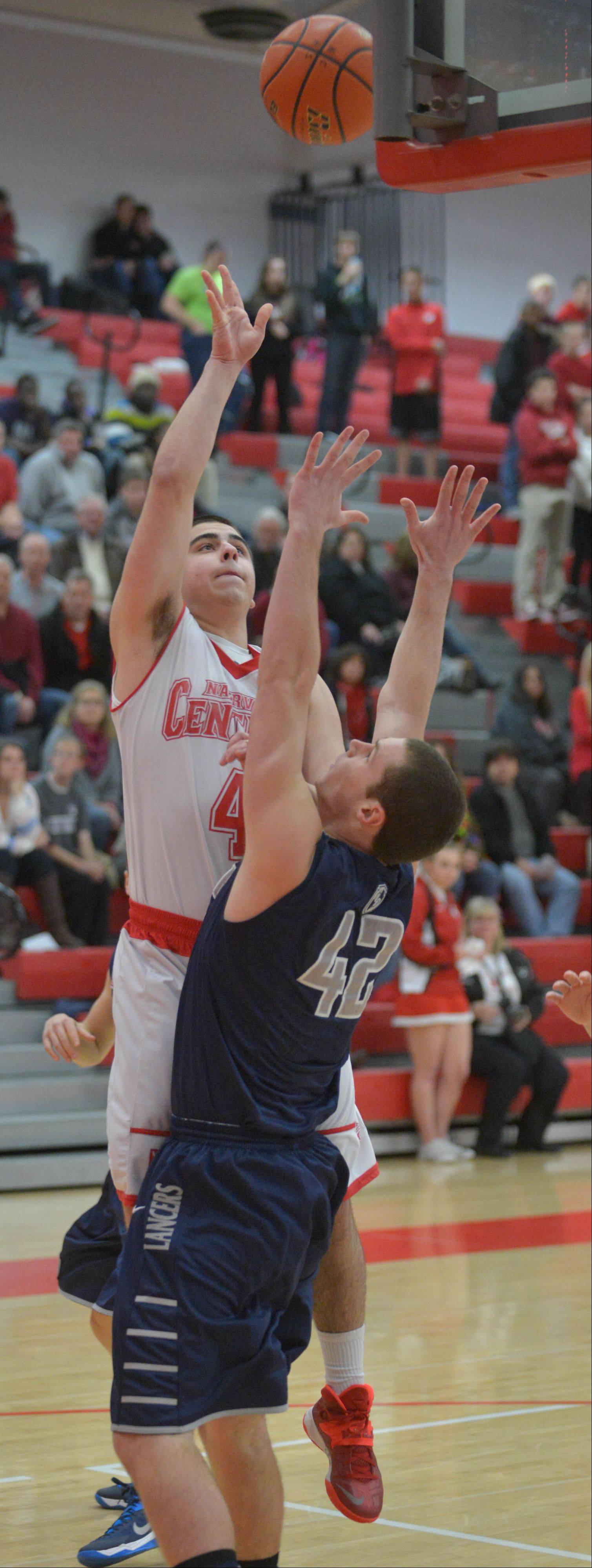 Ryan Antony of Napervile Central takes a shot over John Hower of Lake Park puts up a shot during the Lake Park at Naperville Central boys basketball game Friday.