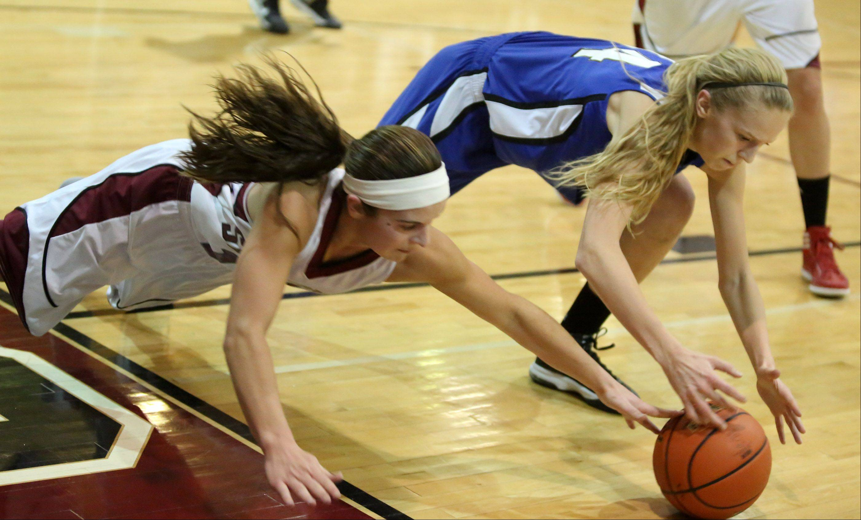 Vernon Hills forward Kasey Firnbach, right, and Antioch guard Ashley Reiser dive to the floor for a loose ball .