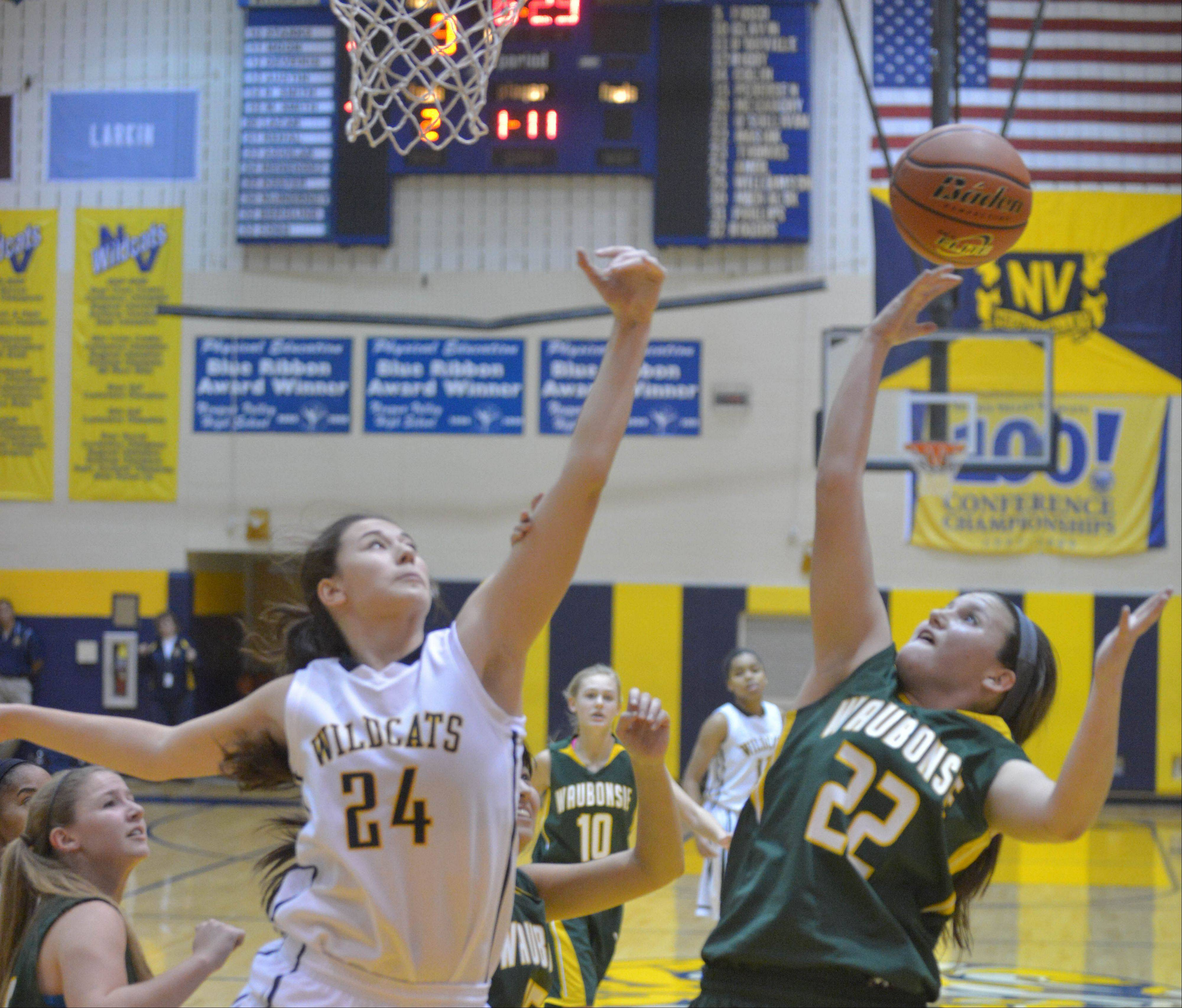 Bryce Menendez, left, of Neuqua and Jordan Masiak of Waubonsie go for a rebound during the Waubonsie Valley at Neuqua Valley girls basketball game Saturday.