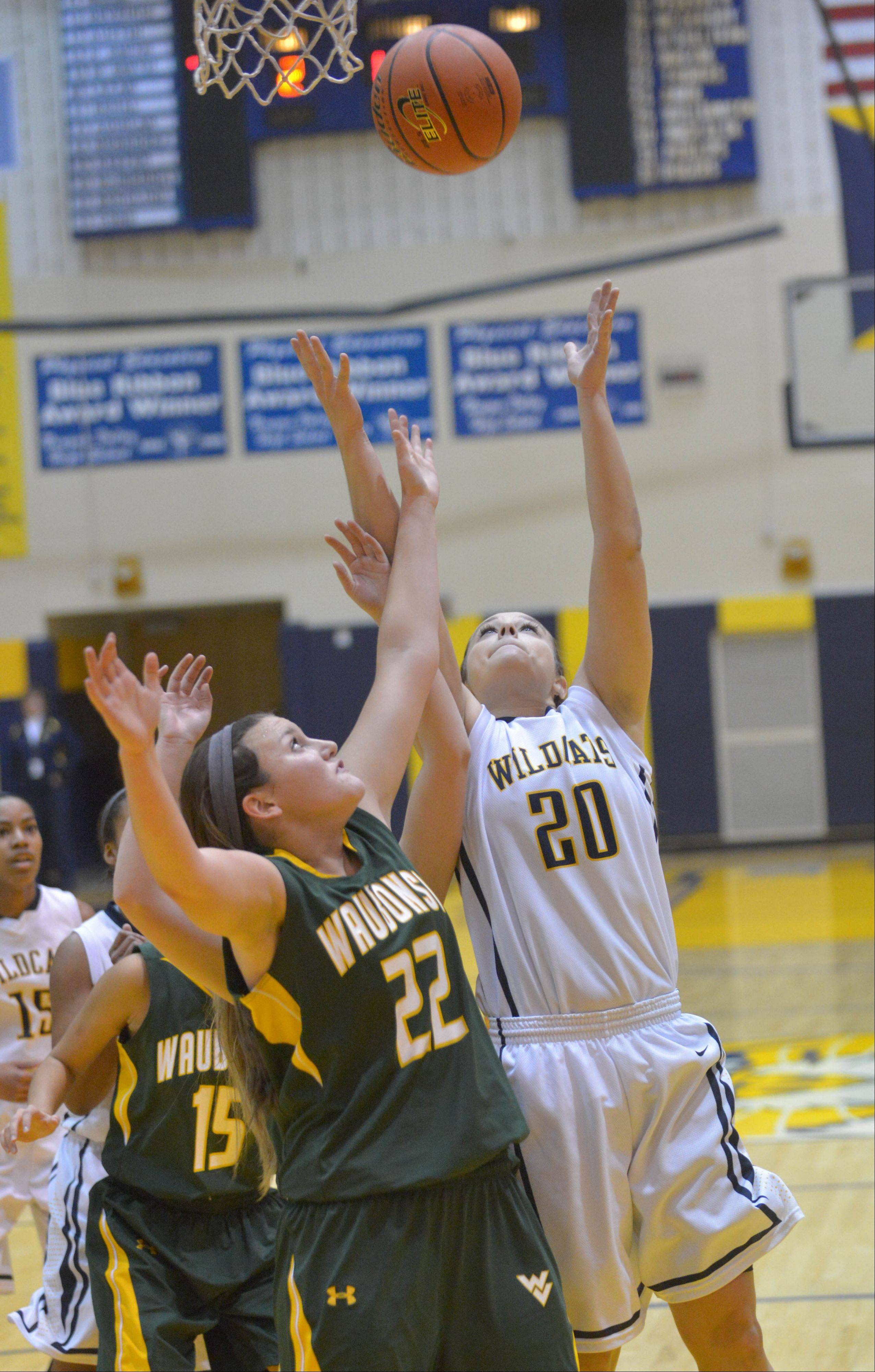 Jordan Masiak of Waubonsie, left, and Niki Lazar go for a rebound during the Waubonsie Valley at Neuqua Valley girls basketball game Saturday.