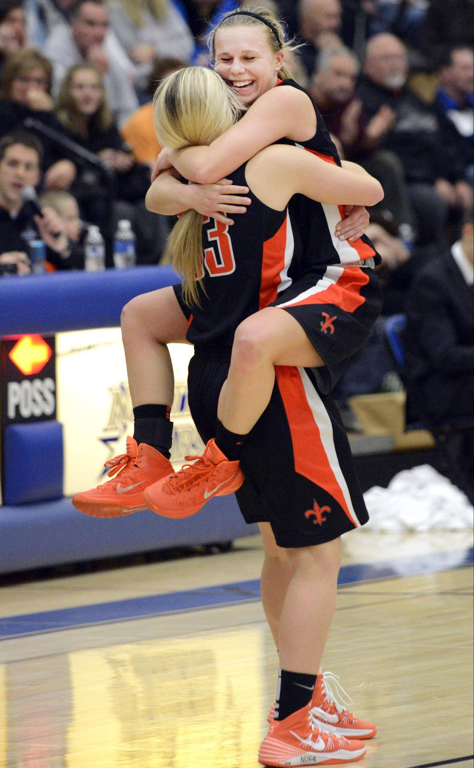 St. Charles East's Amanda Hilton jumps into the arms of teammate Hannah Nowling as time expires in their win Saturday.