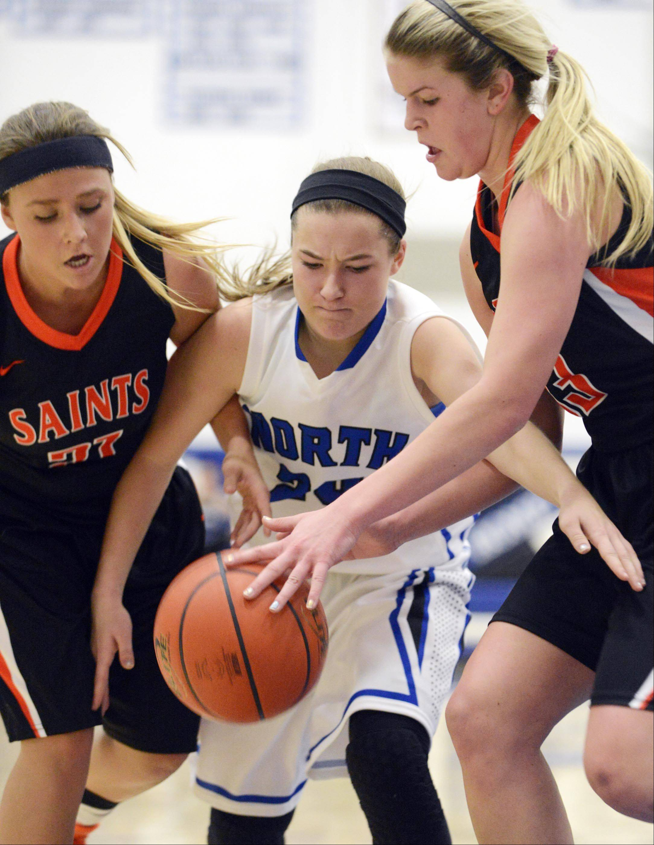 St. Charles East's MacKenzie Meadows and Hannah Nowling surround St. Charles North's Sam Novak Saturday.