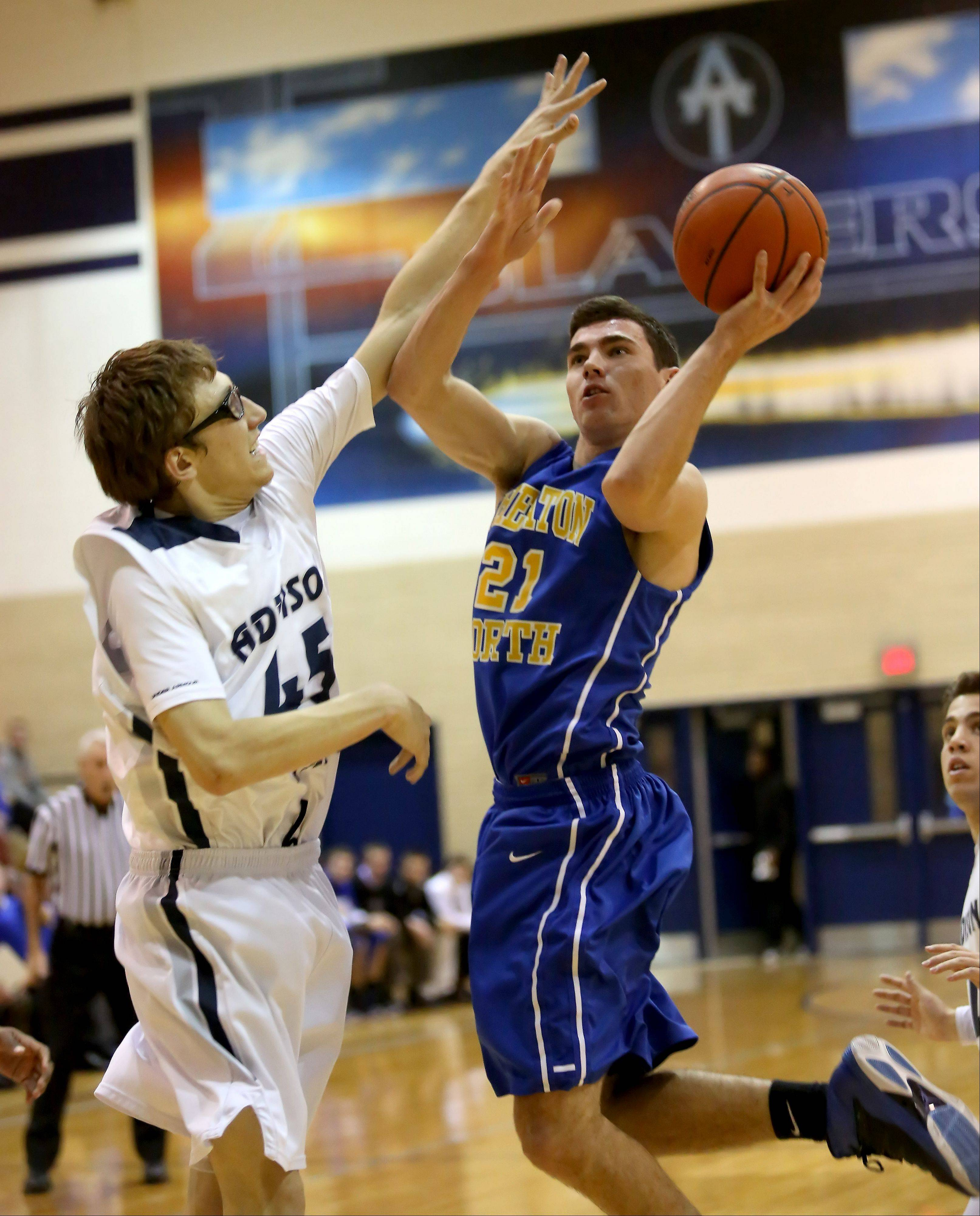 Addison Trail's Joe Villasenor defends, left, as Andrew Slivinski of Wheaton North tries for a basket .