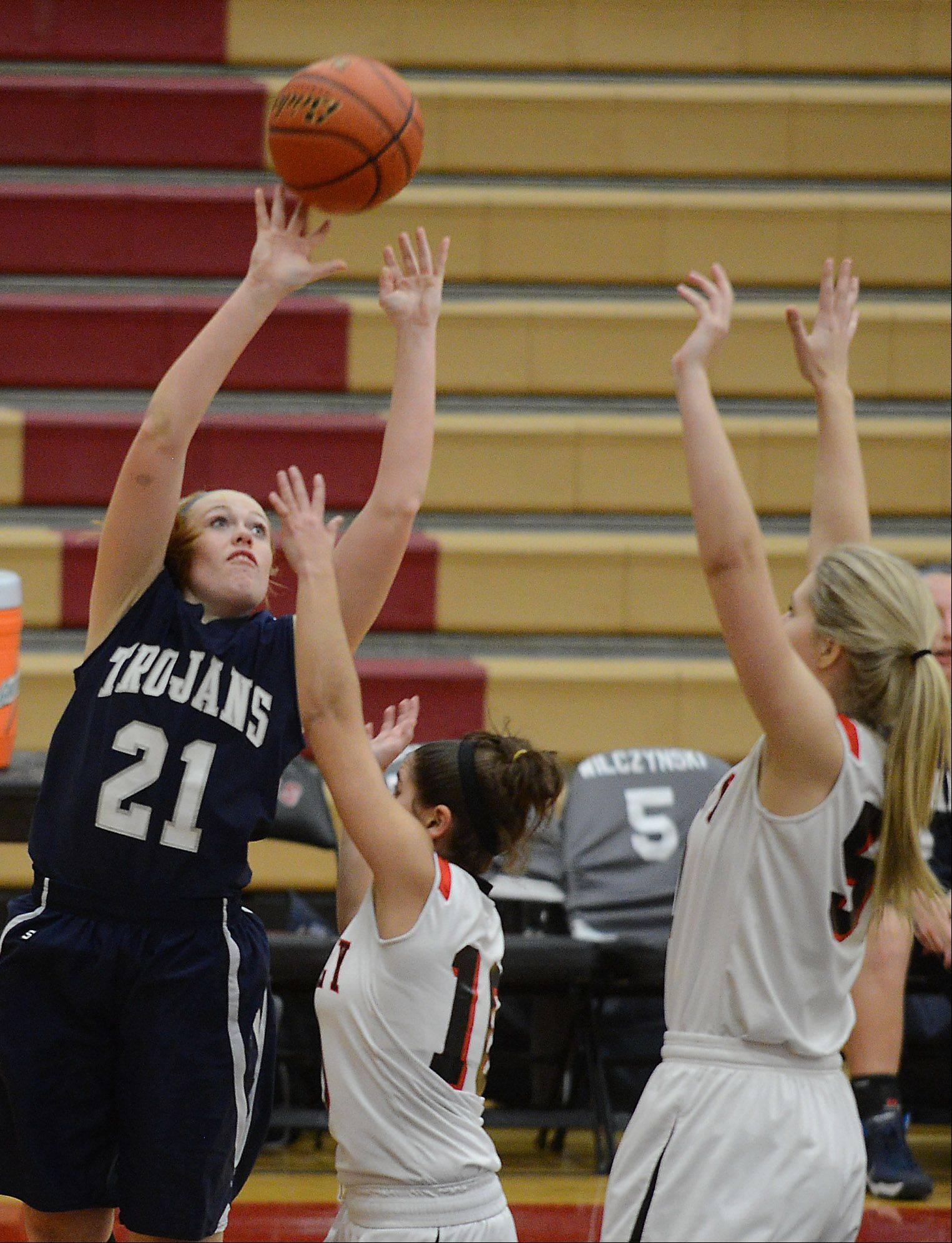 Cary-Grove's Sarah Kendeigh (21) puts up a shot over a pair of Huntley defenders during Monday's game in Huntley.