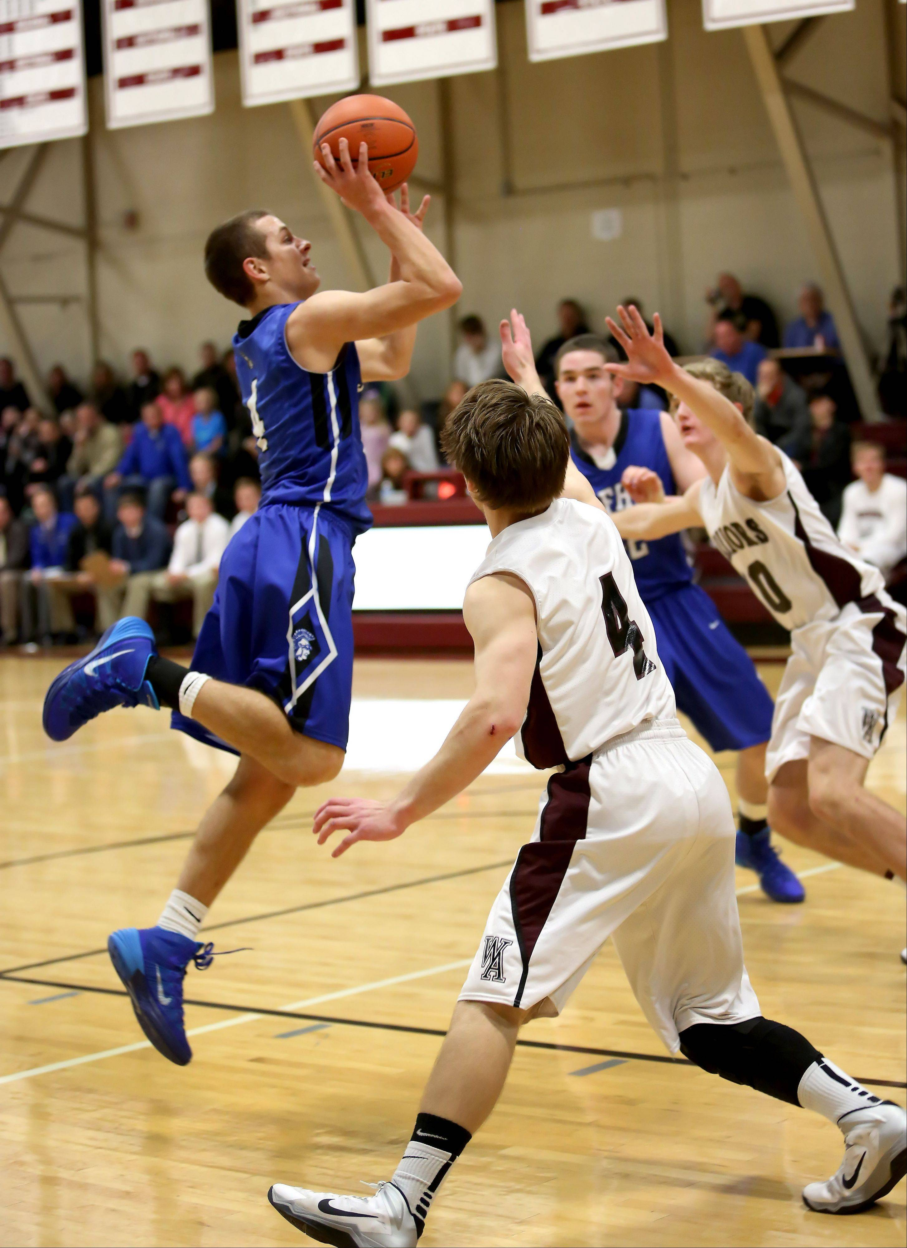 Zach Prociuk of St. Francis, left, goes up for a shot in action against Wheaton Academy during boys basketball in West Chicago on Tuesday.