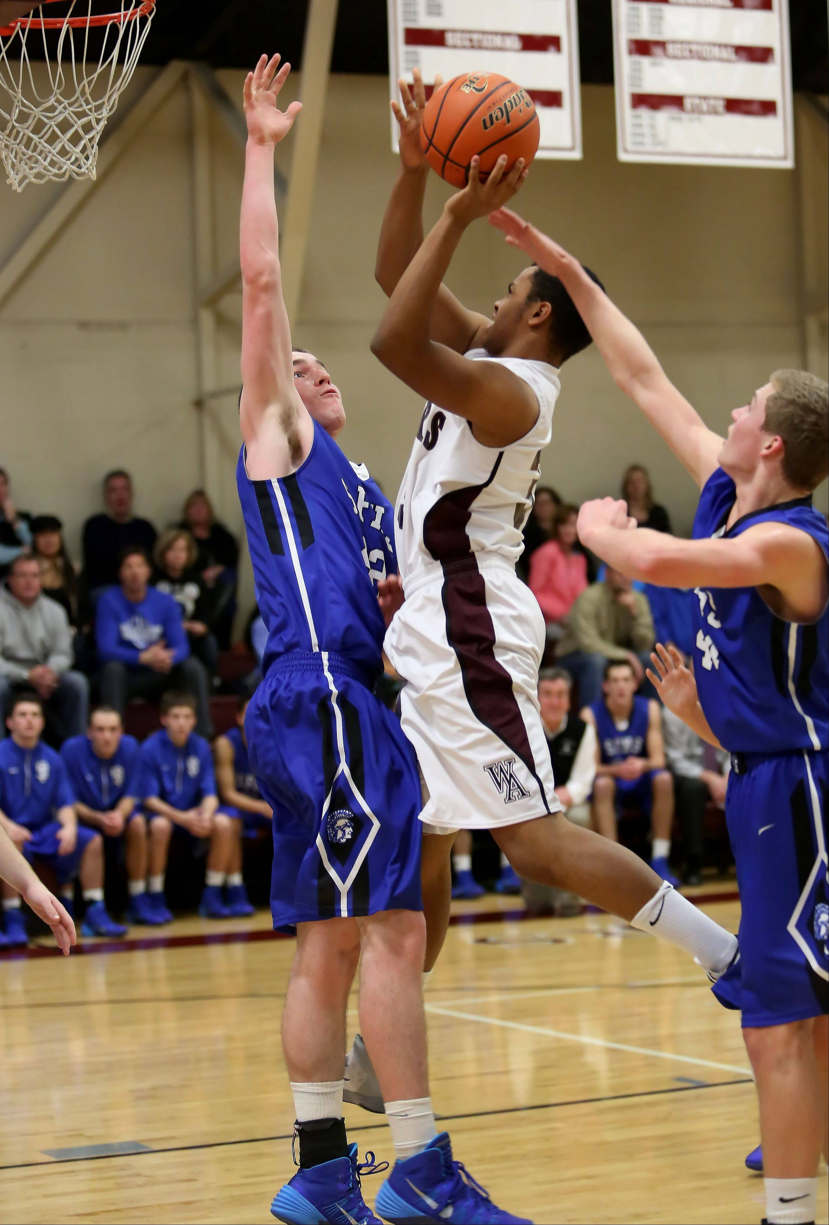 Wheaton Academy's Evan Williams, center, goes up for a basket as Kilian Brown of St. Francis defends, left, during boys basketball in West Chicago on Tuesday.