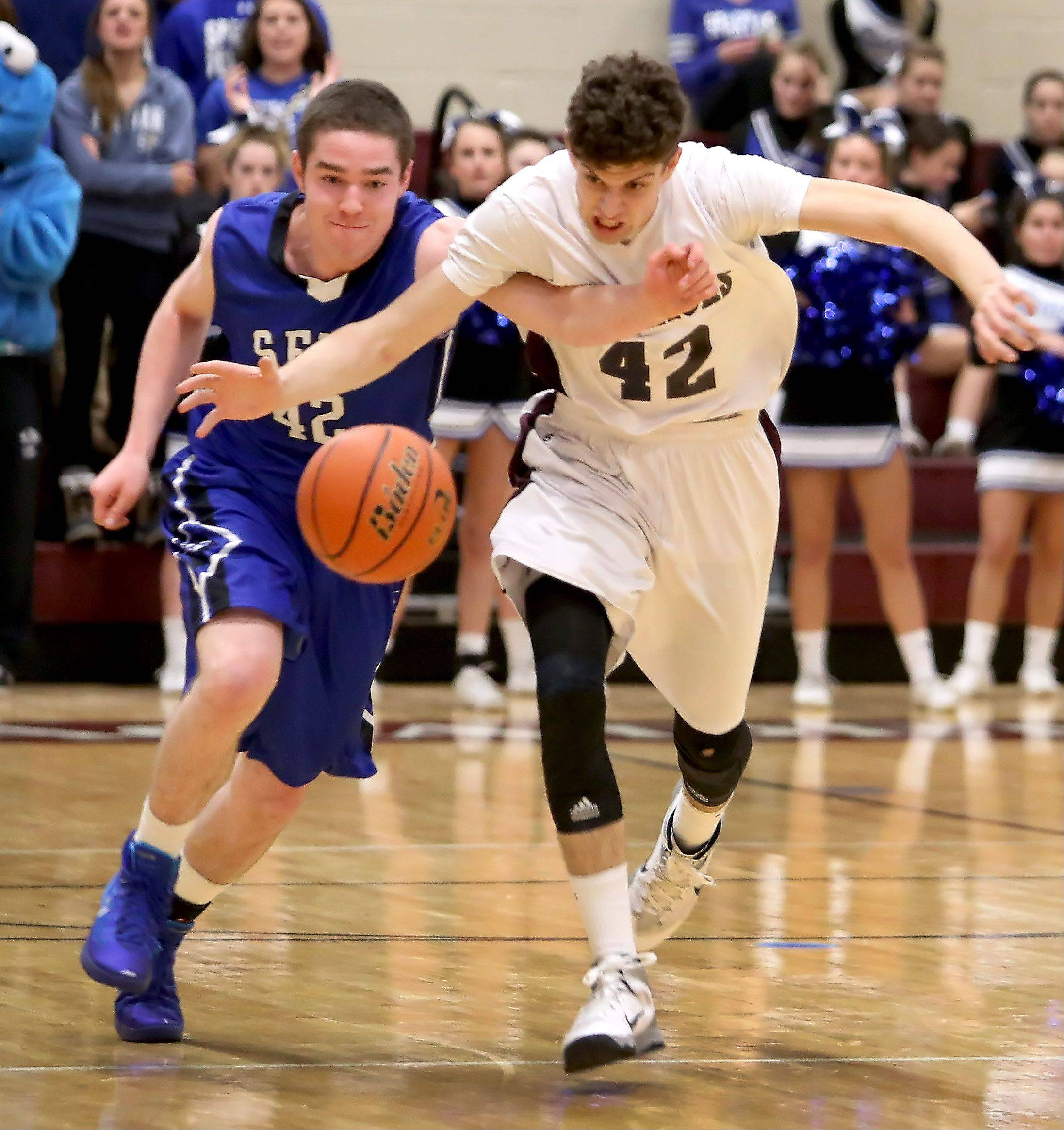 Kilian Brown, left, of St. Francis and Chandler Fuzak, right, of Wheaton Acadamy, chase down a loose ball during boys basketball action in West Chicago on Tuesday.