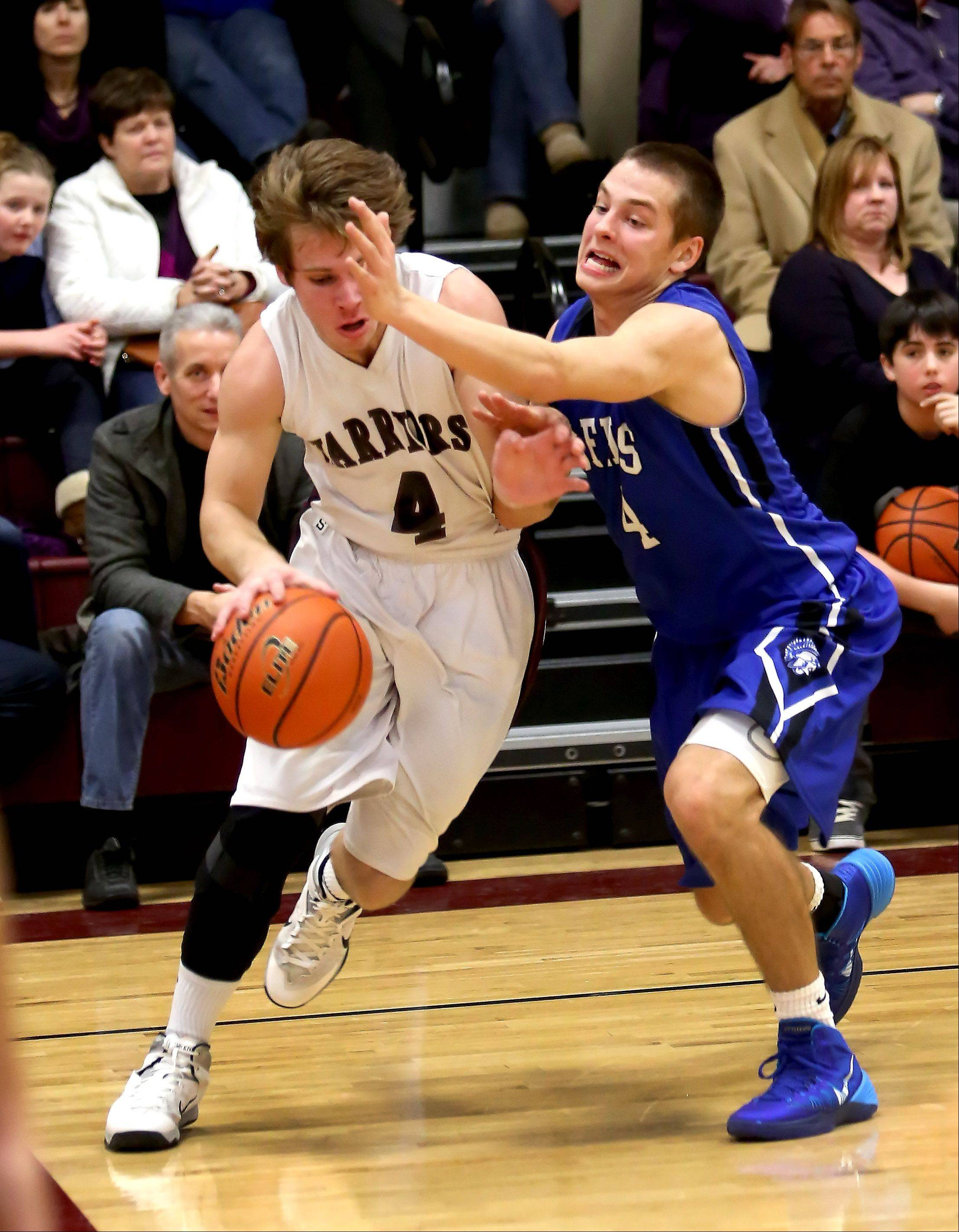 Wheaton Academy's Chris Johnson, left, drives around Zach Prociuk of St. Francis during boys basketball in West Chicago on Tuesday.