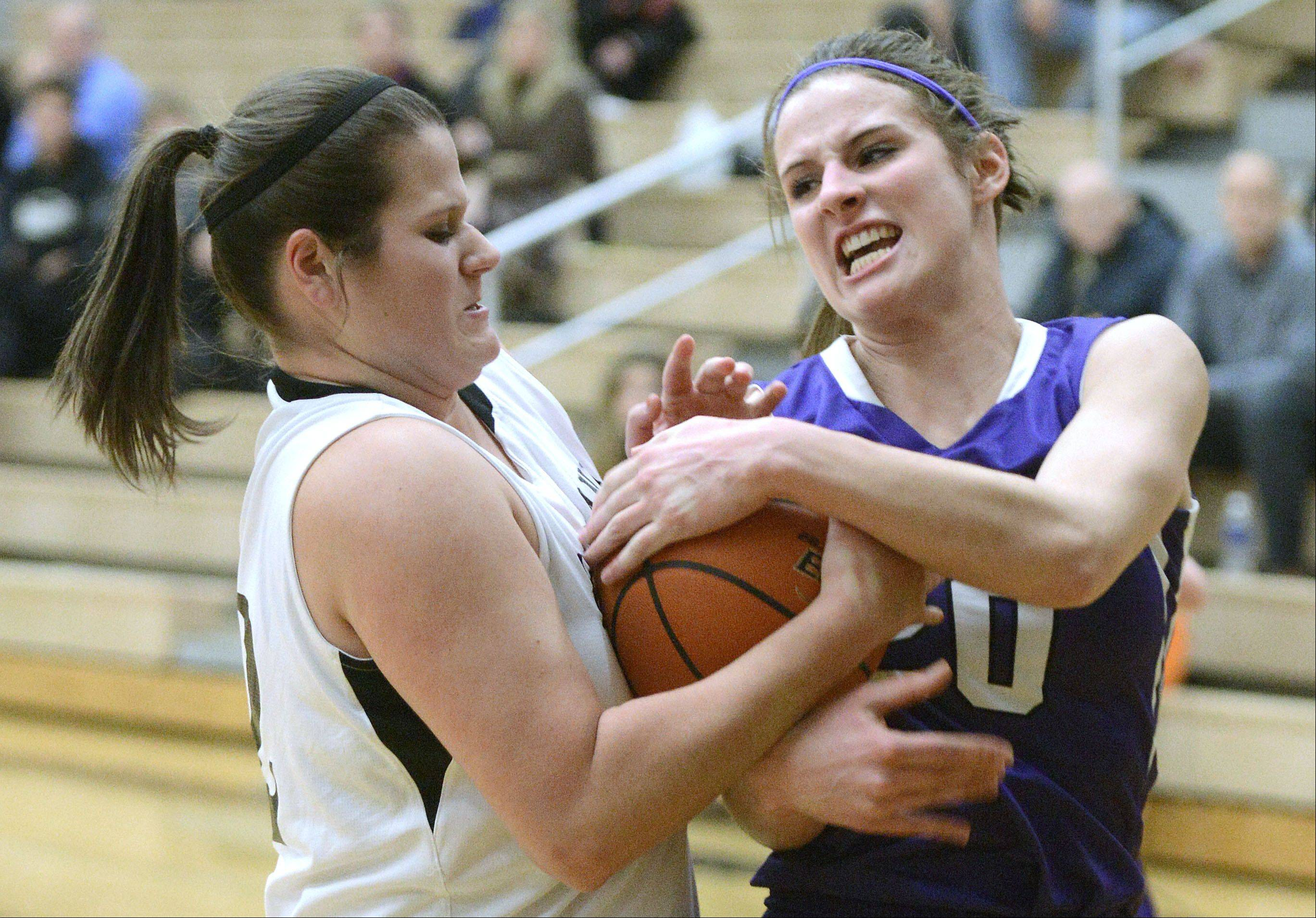 Kaneland's Kelly Wallner and Rochelle's Abby Gould wrestle for the ball in the first quarter on Tuesday, December 10.