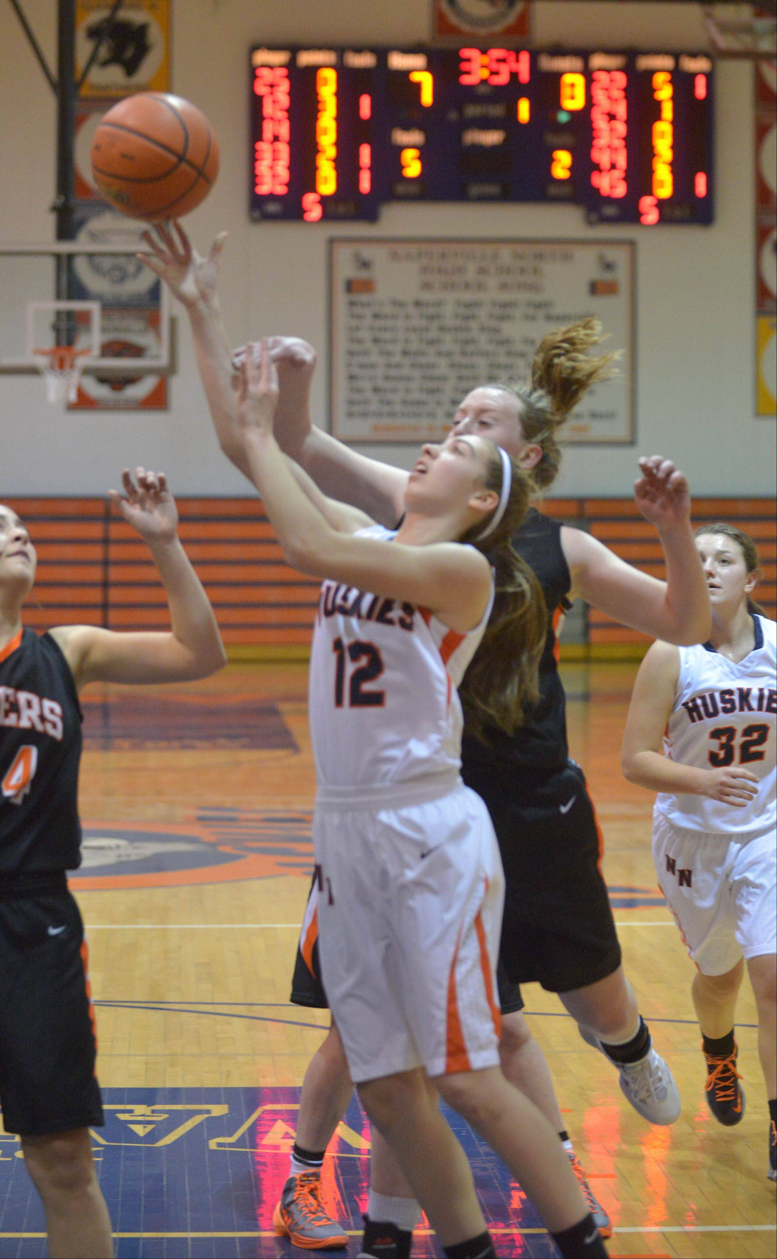 Laurel Pereira of Naperville North takes one to the net during the Wheaton Warrenville South at Naperville North girls basketball gameTuesday.