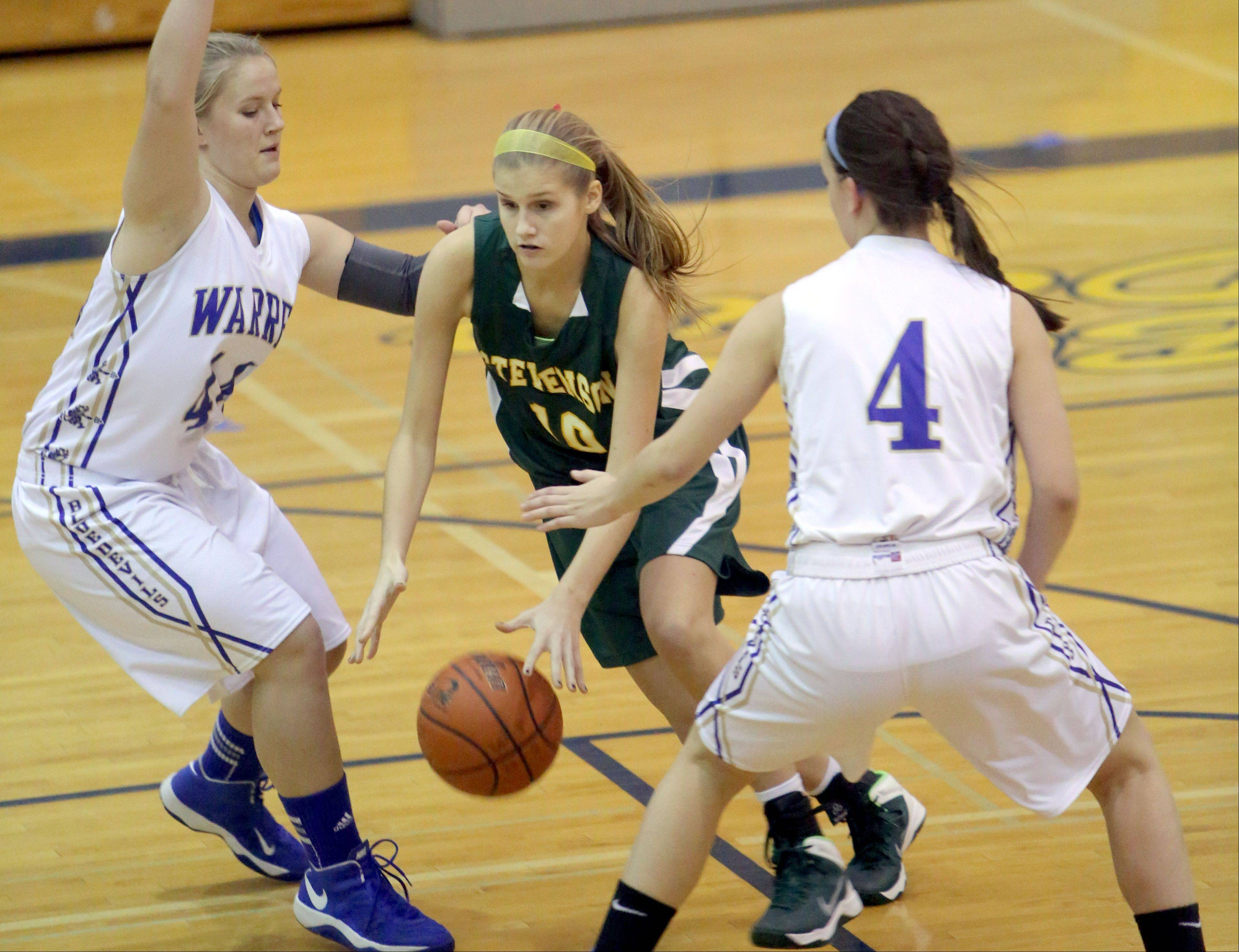 Stevenson's Chloe Ekenberg, middle, drives through Warren's Keely Knobbe, left, and Kylie Nedelka on Tuesday night in Gurnee.