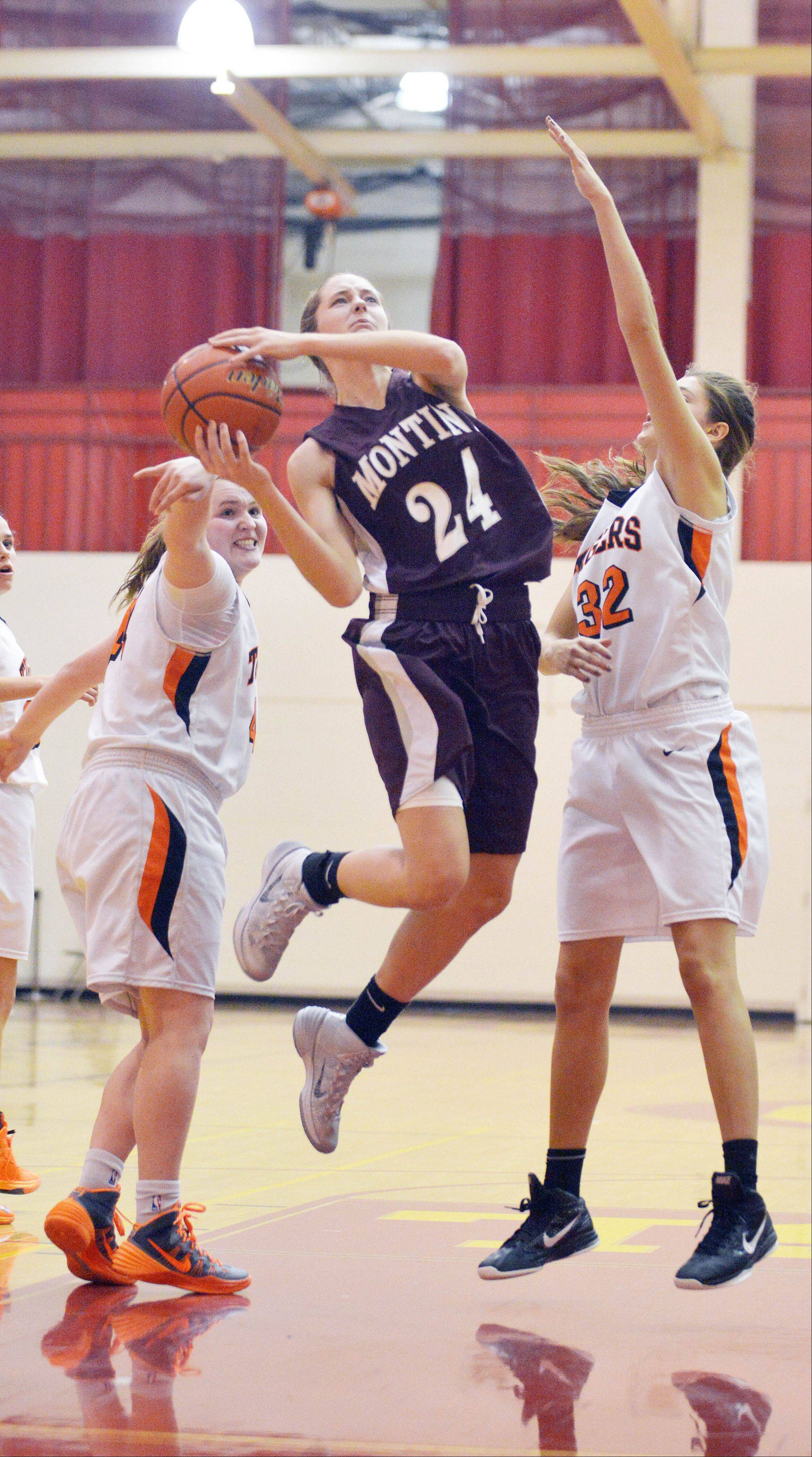 Kateri Stone of Montini, center, takes one to the net during the Wheaton Warrenville South vs. Montini girls basketball game at the Schaumburg tournament Friday. Olivia Linebarger, left, and Erin Zappia were attempting to block the shot.