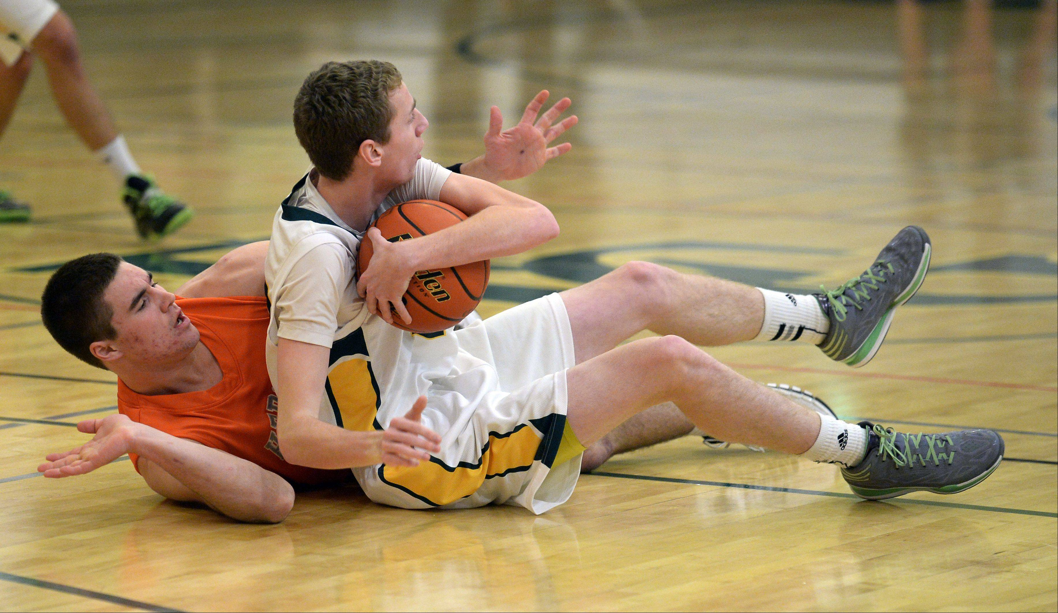 Elk Grove's Dan Hadler and Hersey's Grant Burke mix it up on the floor in the first quarter as they vie for control of the ball Thursday in Elk Grove.