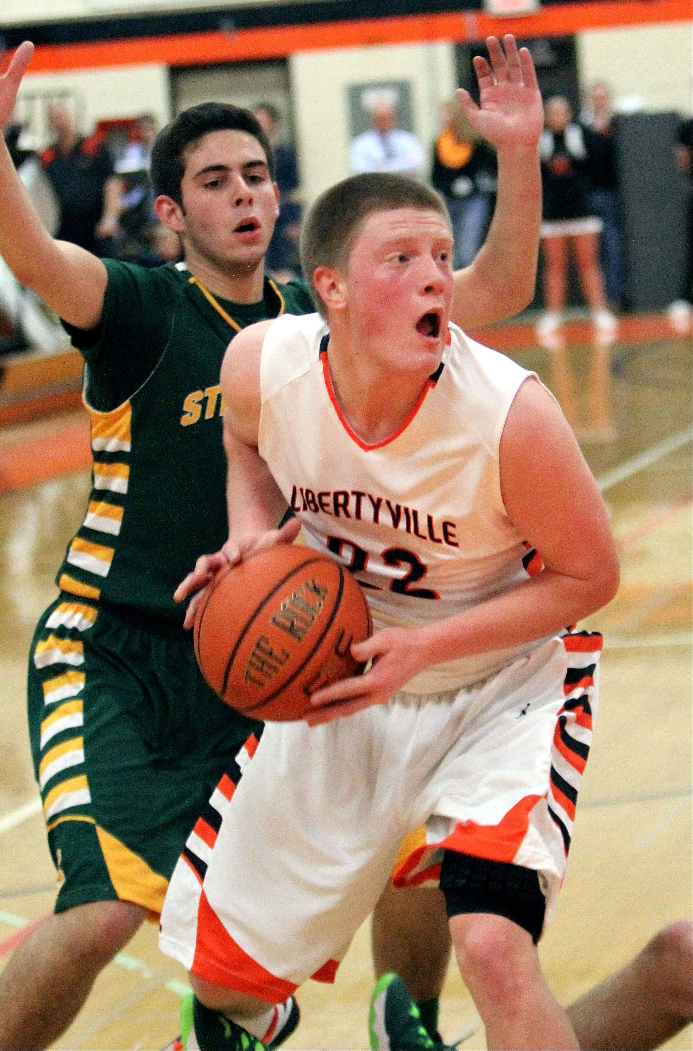 Libertyville's Jack Lipp, right, drives past Stevenson's Parker Nichols.