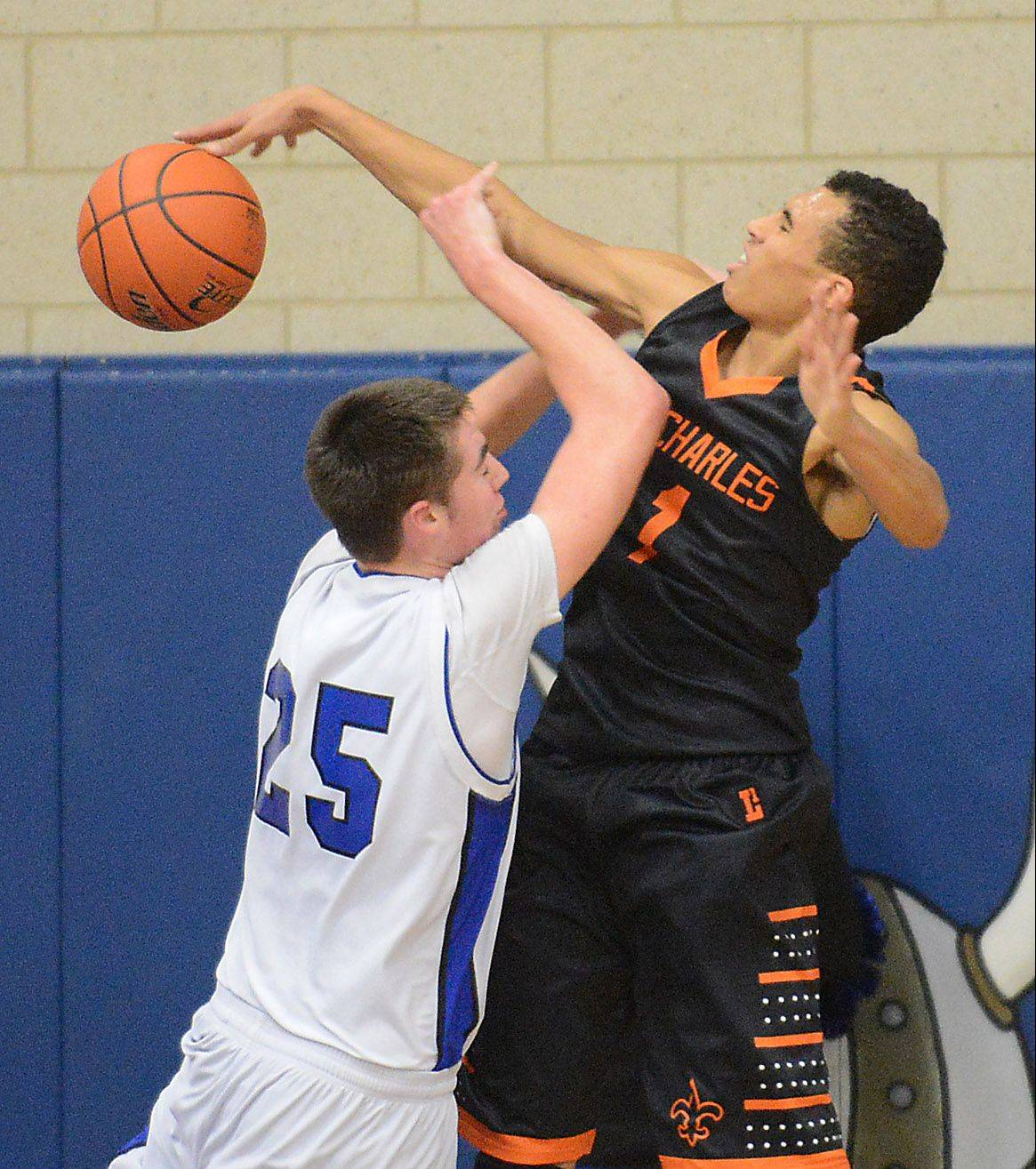 St. Charles East's AJ Washington blocks a shot by Geneva's Nate Navigato.