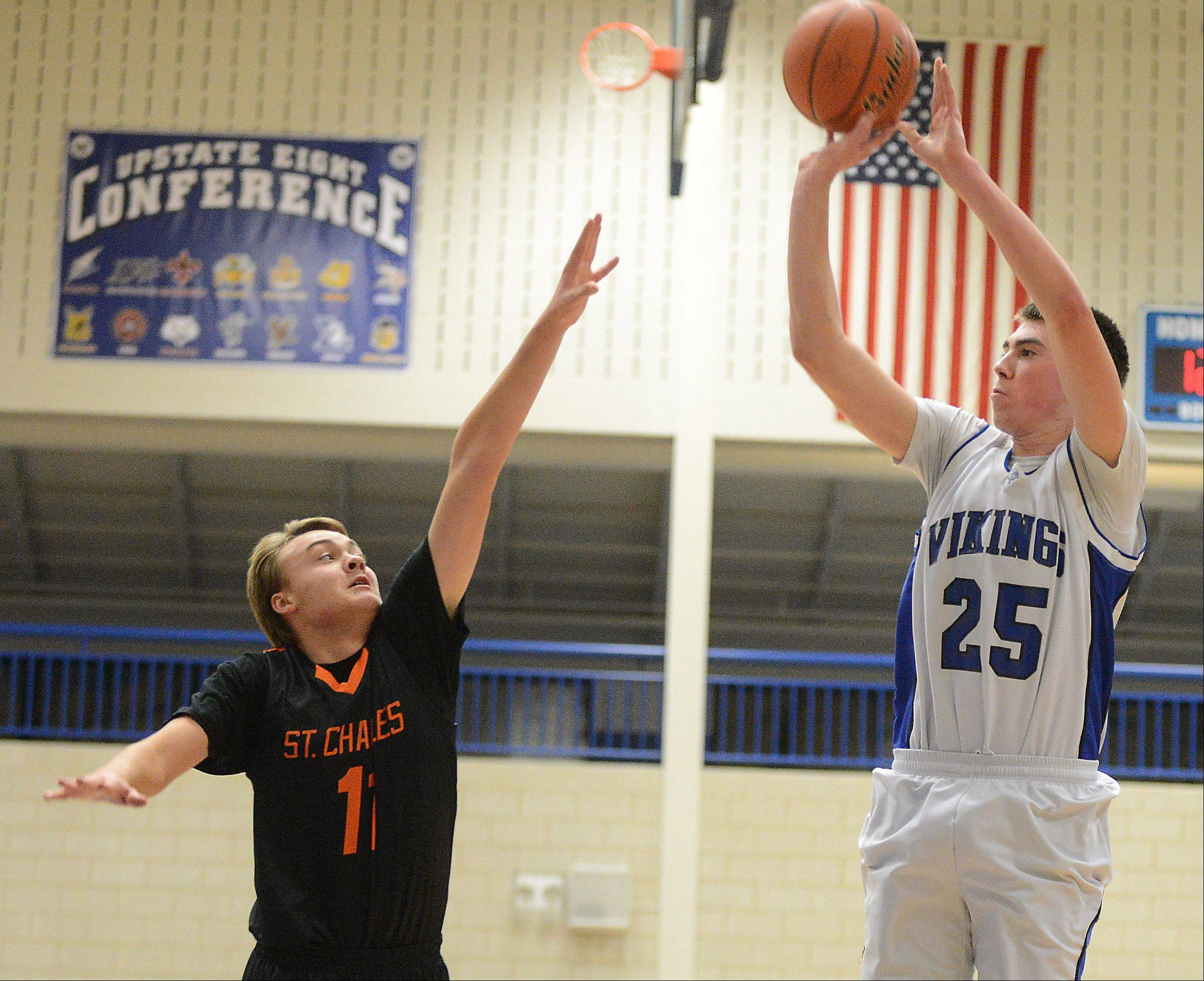 Geneva's Nate Navigato (25) shoots over St. Charles East's Mick Vyzral (11) during Friday's game in Geneva.