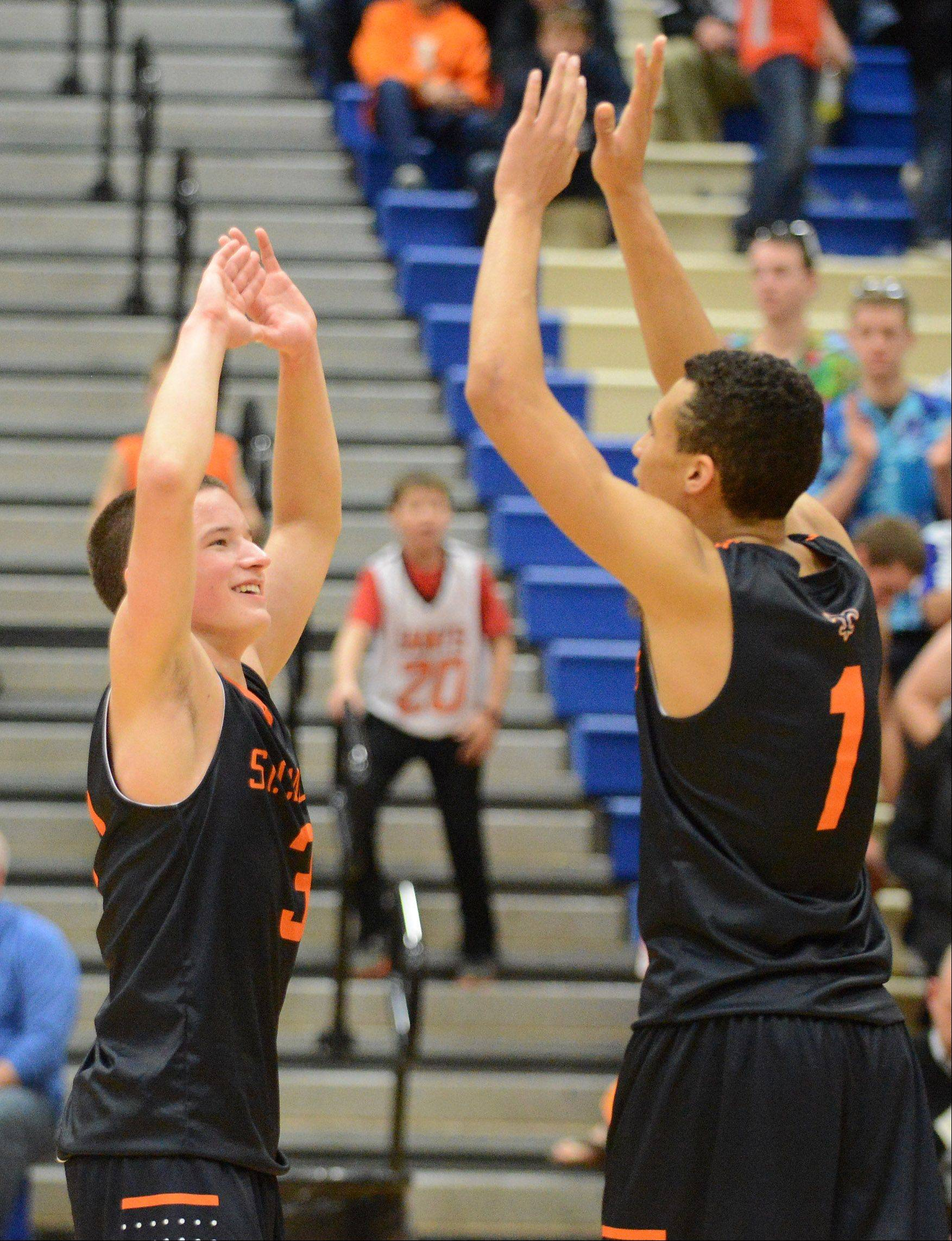 St. Charles East's Cole Gentry (3) and AJ Washington (1) celebrate their win following Friday's game in Geneva.