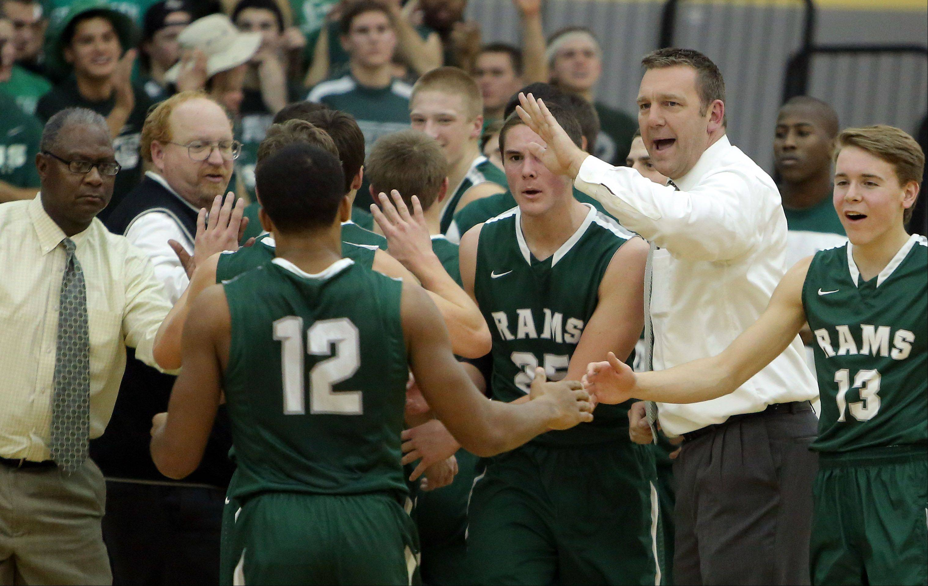 Grayslake Central coach Brian Moe, right, encourages his team during a timeout Friday night at Grayslake North.