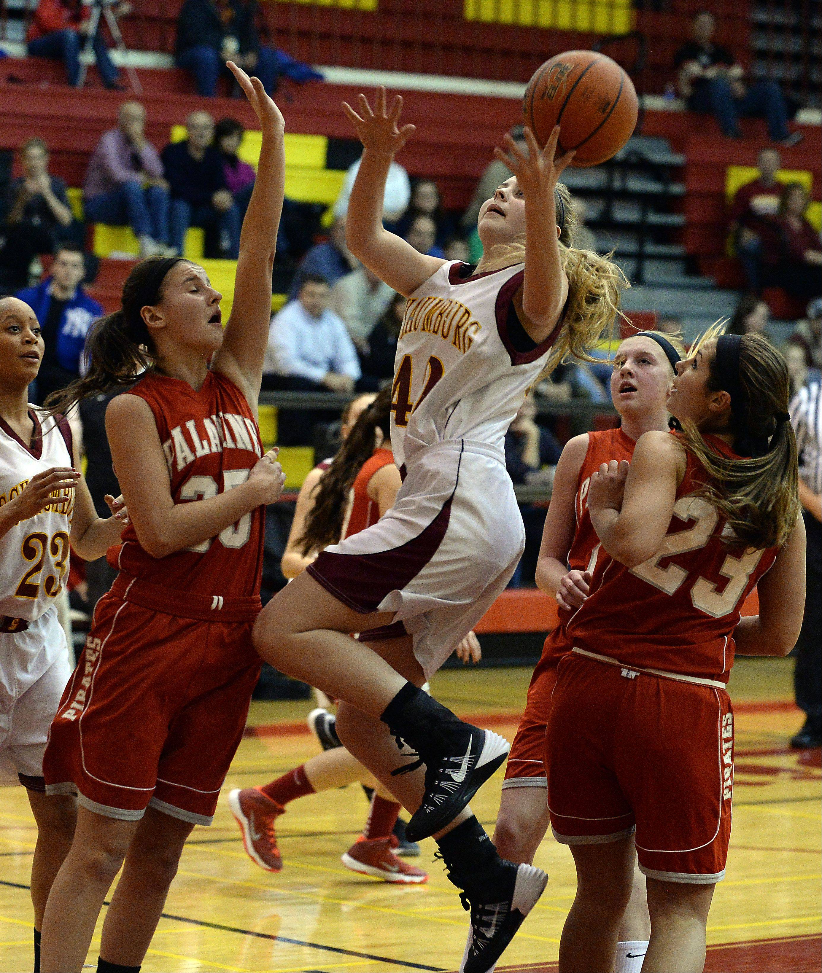 Schaumburg's Mallory Gerber delivers as Palatine's Erin Mayer and Morgan Gallagher block in the first quarter.