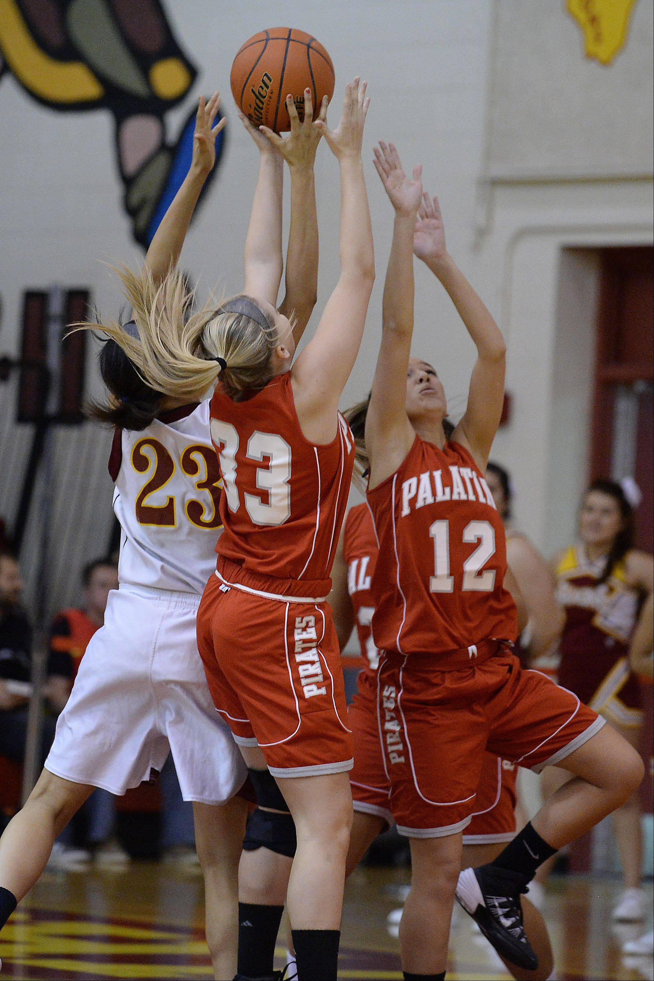 Palatine's Kirsten Allen and Rachel Fritz battle for control with Schaumburg's Jada Blackwell in the first half.