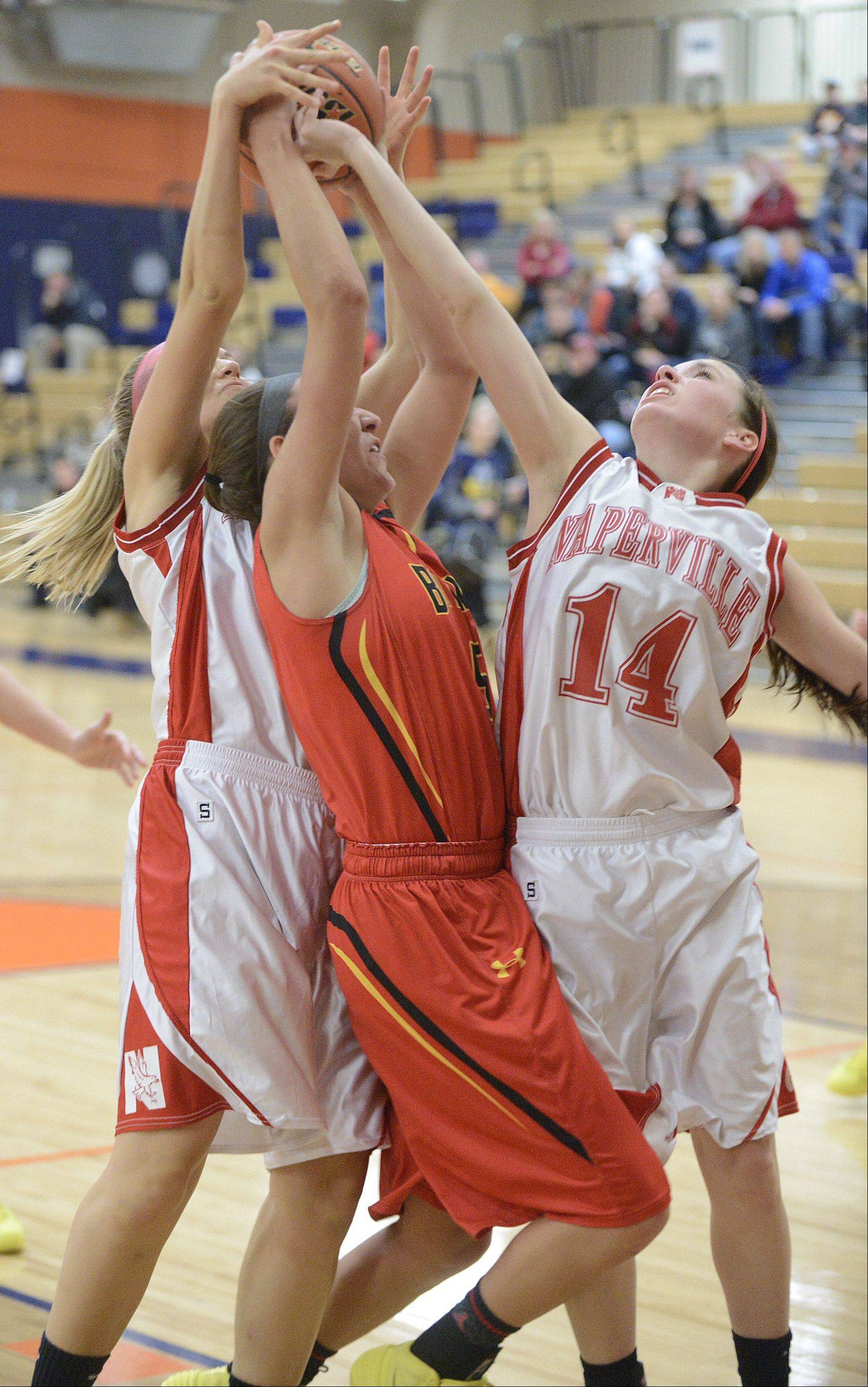 Batavia's Liza Fruendt is sandwiched by Naperville Central's Kotryna Staputyte and Emily Kraft while grabbing and fighting for a rebound in the second quarter on Saturday.