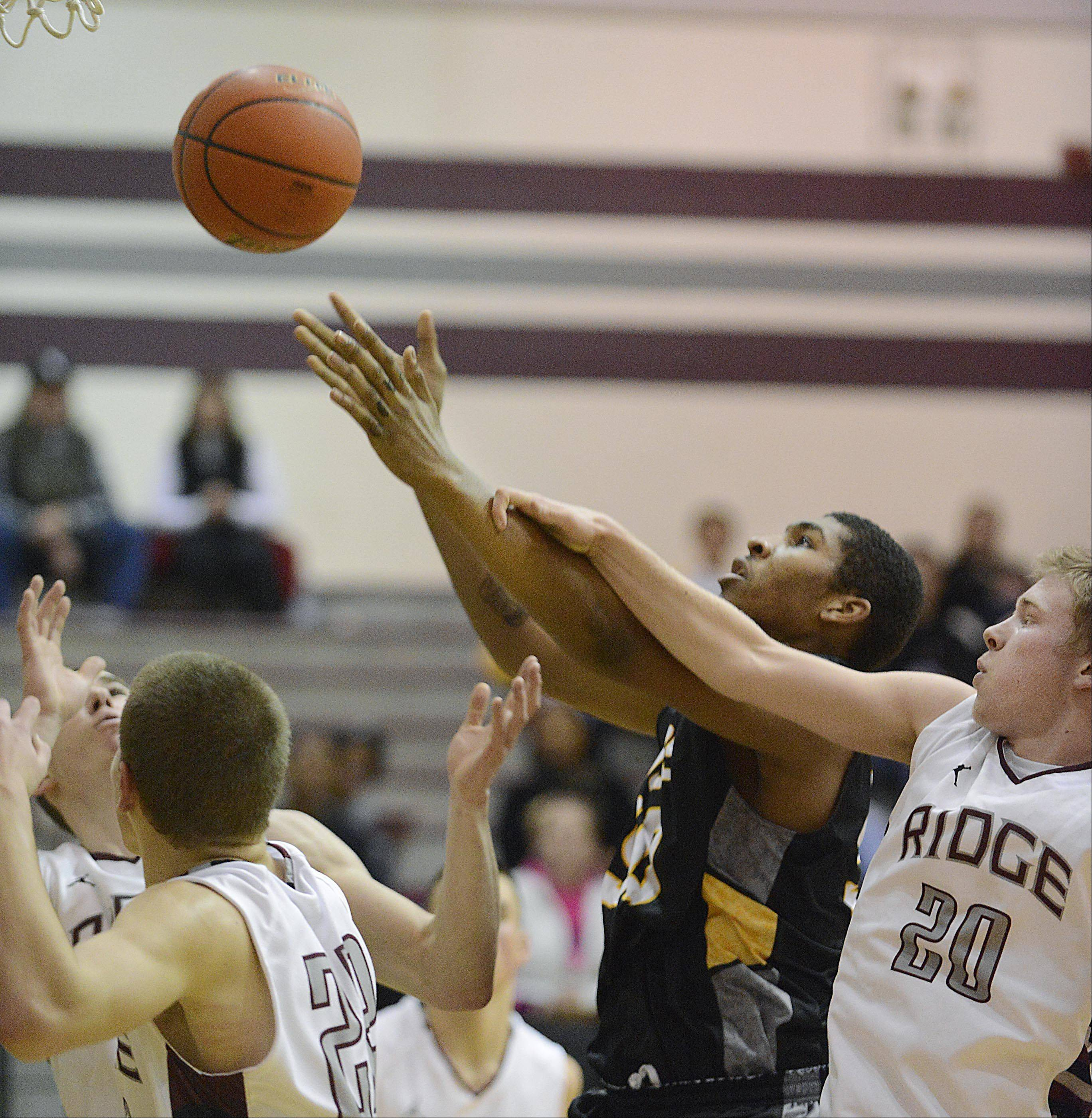 Jacobs' Robert Grant stretches for a rebound in a host of Prairie Ridge players Tuesday in Crystal Lake.