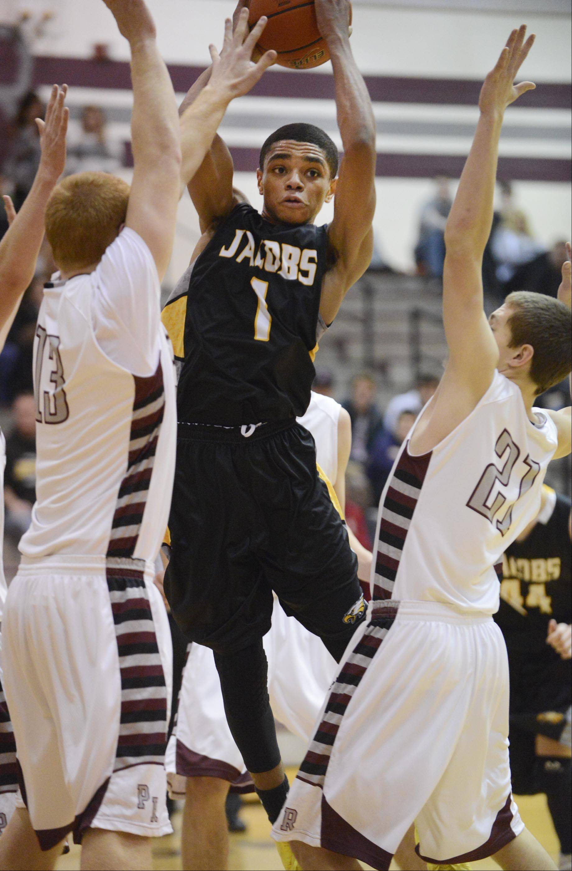 Jacobs' Kenton Mack looks for a teammate between Prairie Ridge's Kody Peterson and Matt Perhats .