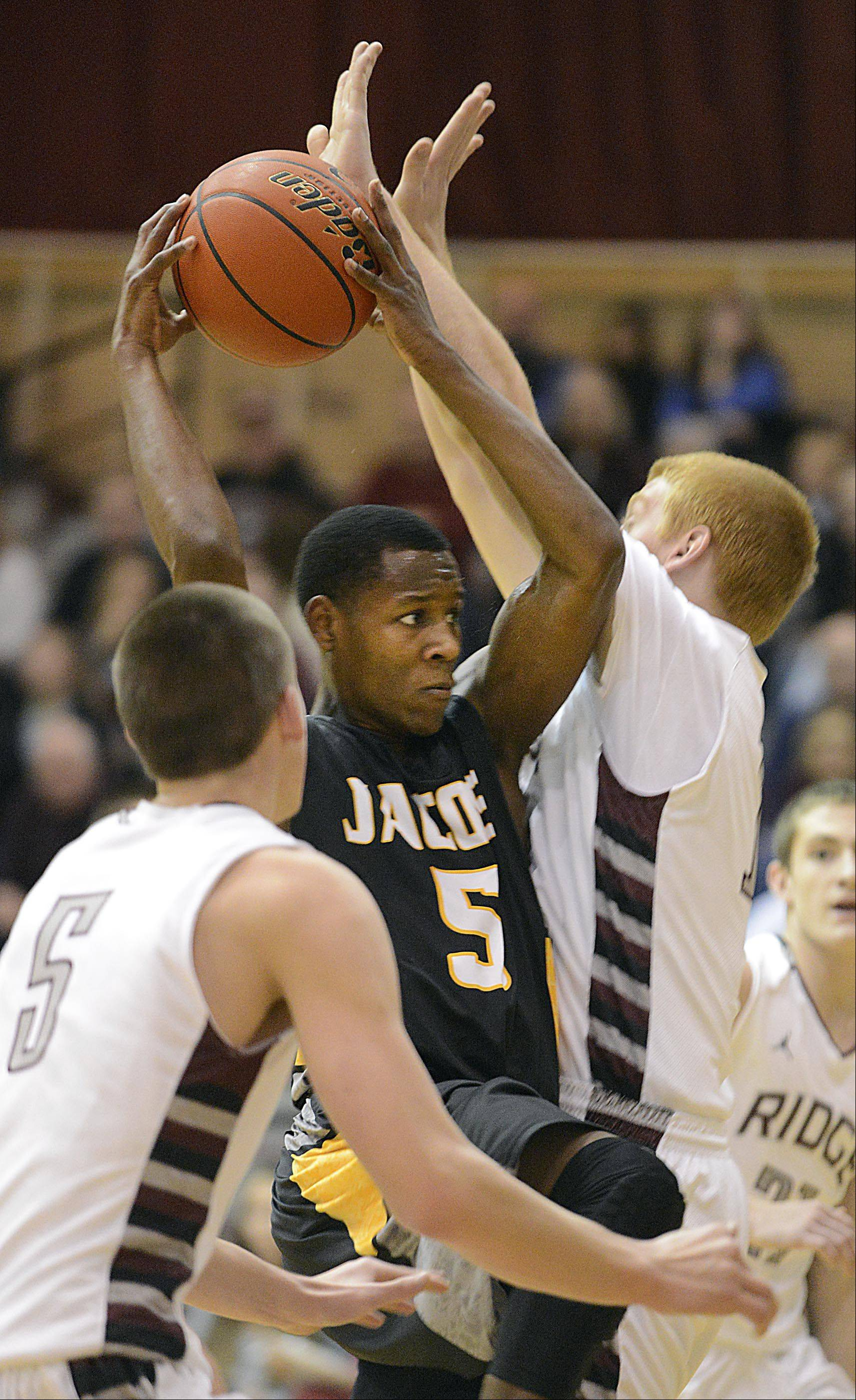 Jacobs' Chris Orange drives and looks for a teammate between Prairie Ridge's Michael Bradshaw and Kody Peterson.