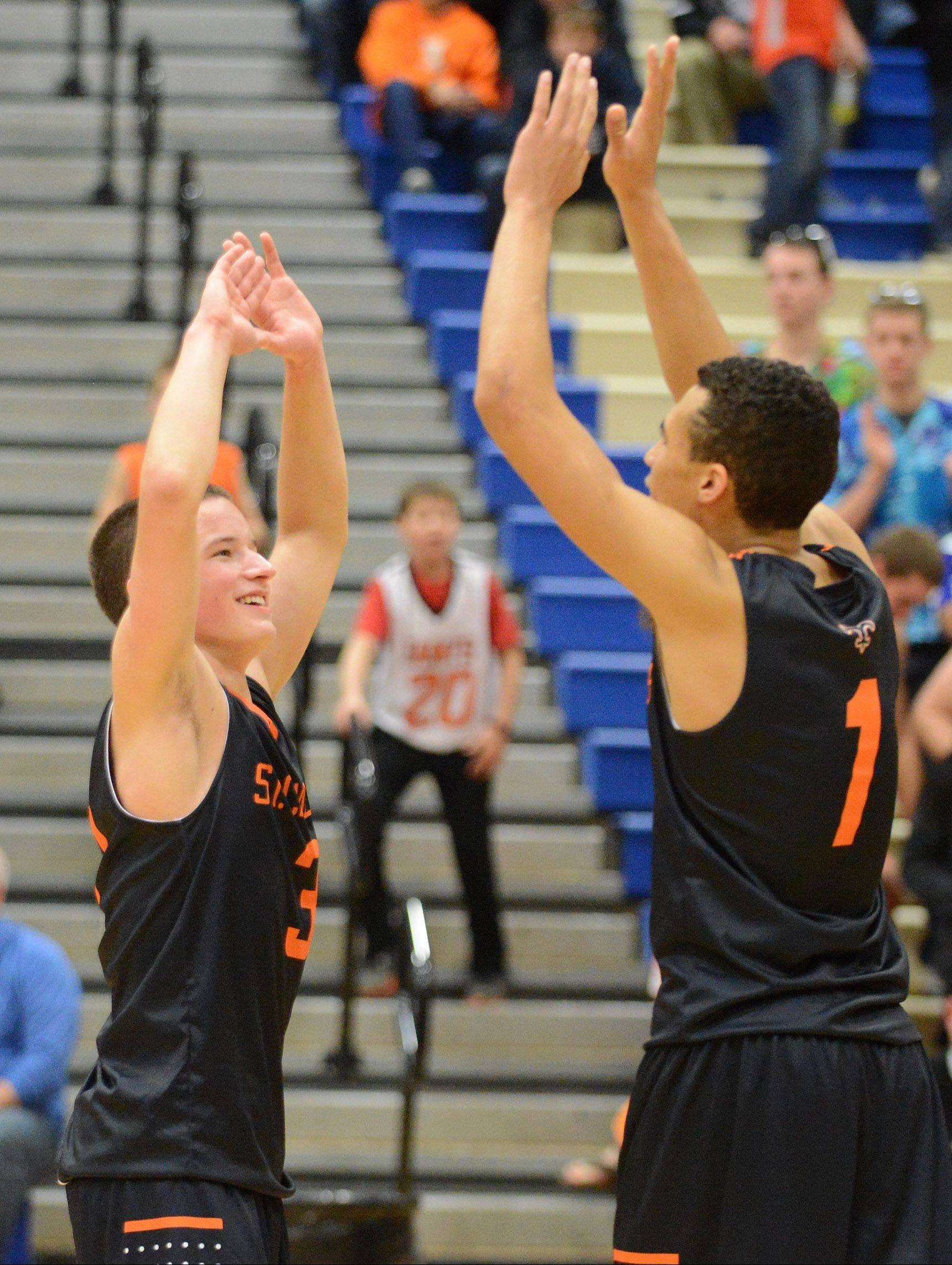 St. Charles East's Cole Gentry (3) and AJ Washington celebrate their win over Geneva last Friday -- one the Saints needed to avoid falling to 0-3 in the Upstate Eight River.