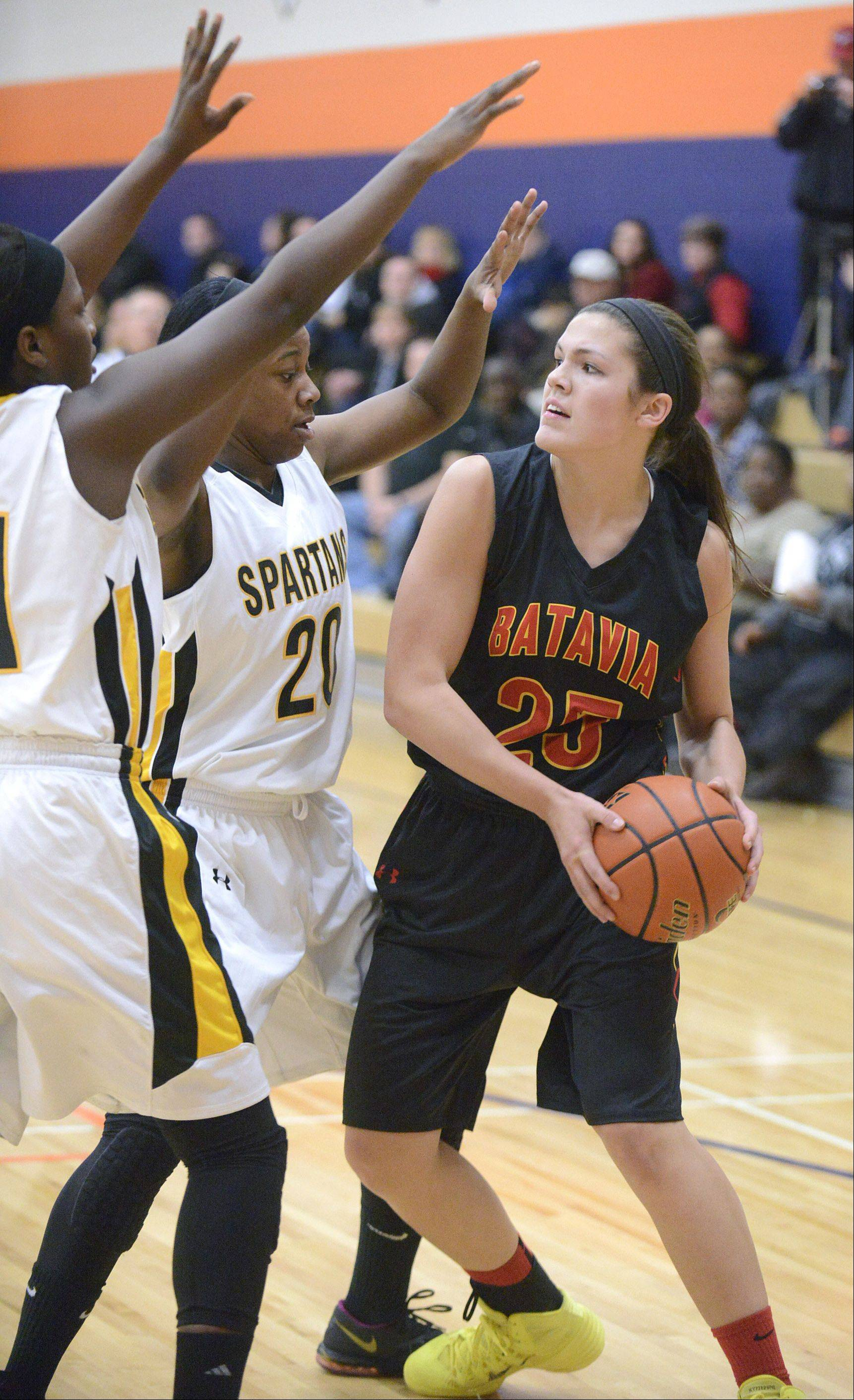 Batavia's Hannah Frazier attempts to pass around Marian Catholic's Ashton Millender and Dajhae Mullins in the first quarter on Wednesday, December 18.
