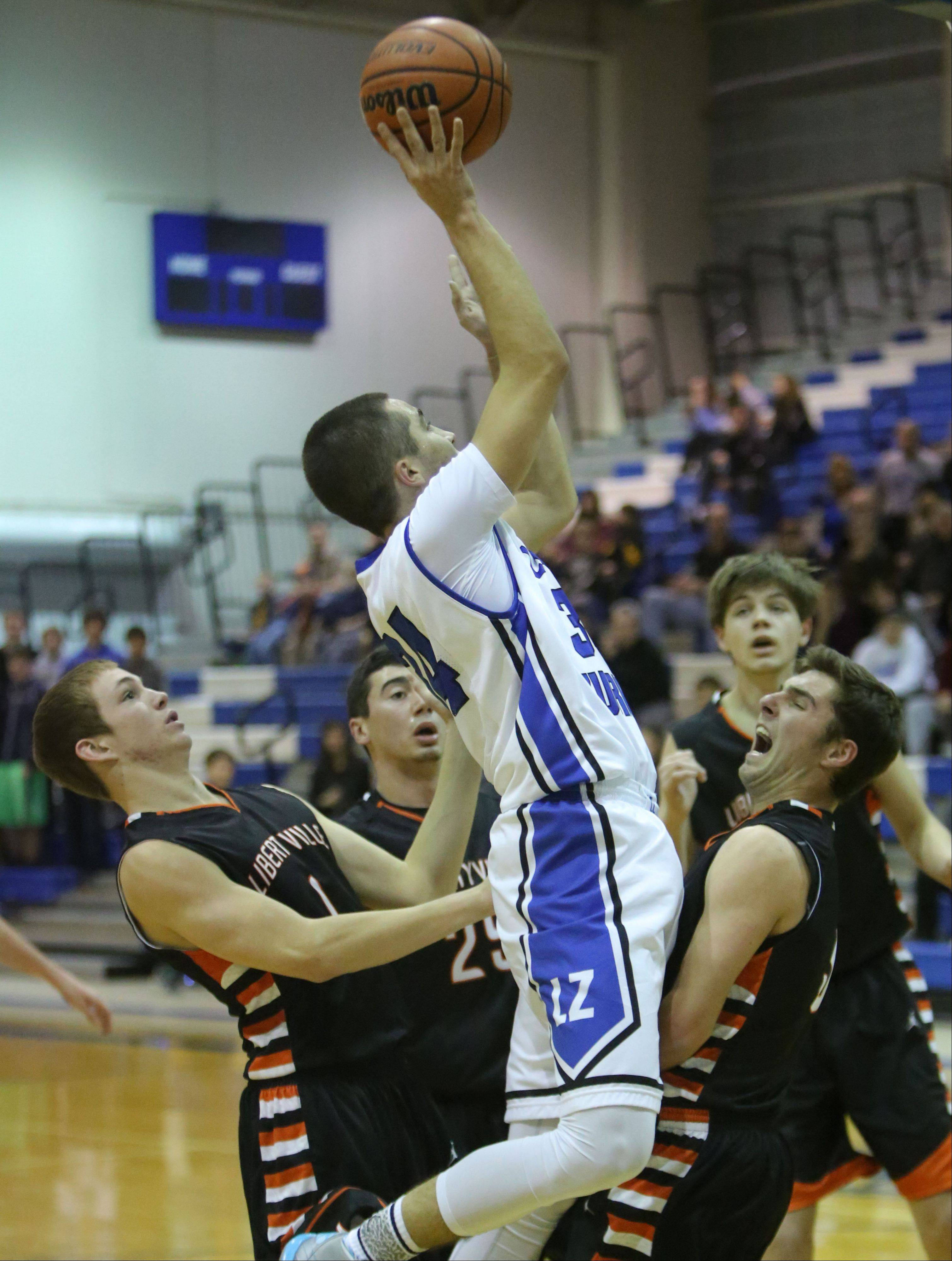 Lake Zurich's Mike Travlos, middle, drives on Libertyville players , from left, Brian Scanlan, Johnny Vernasco and Matt Reed.