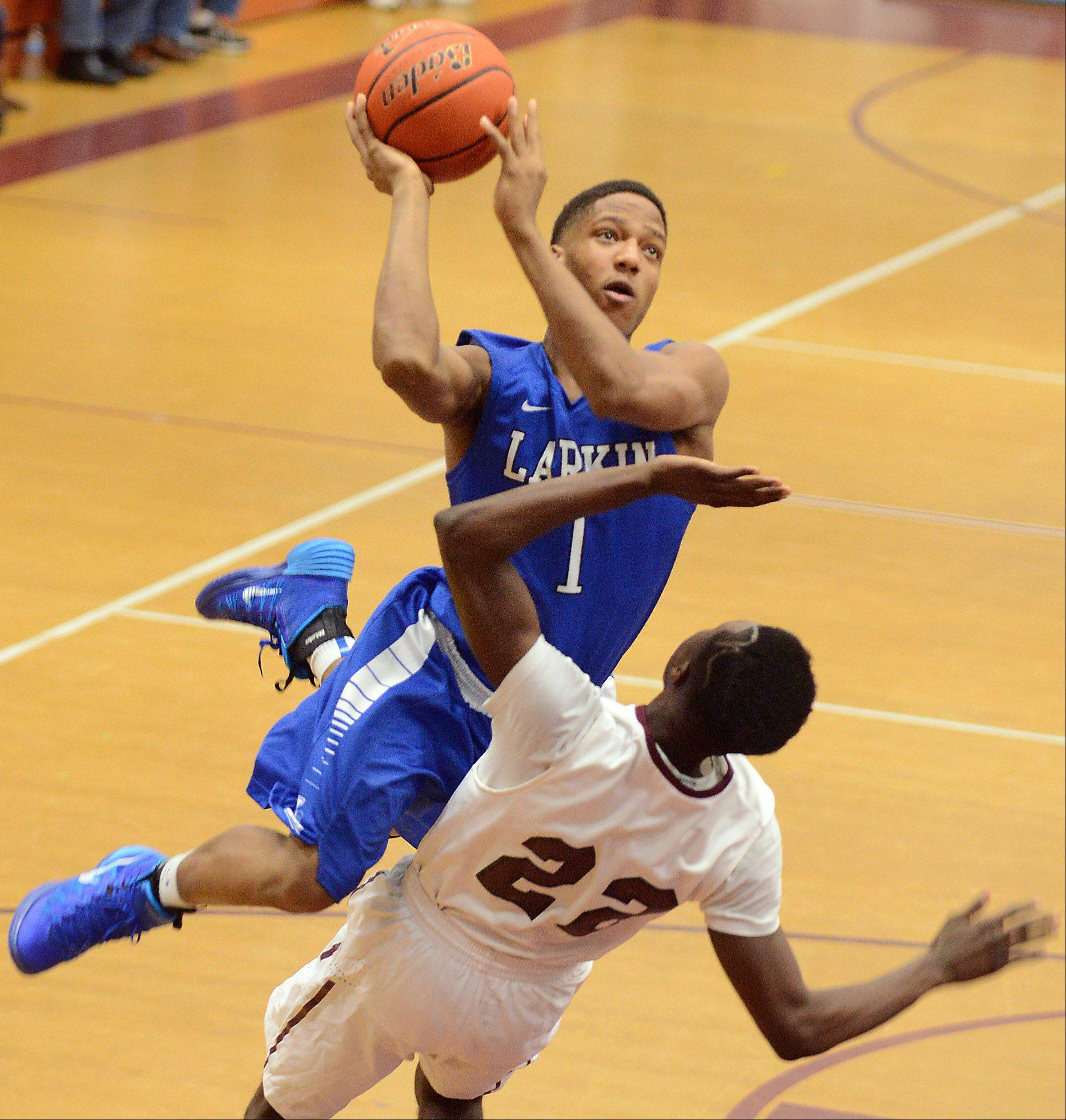 Larkin's Charles Sanders (1) drives over Elgin's Desmond Sanders (22) during Thursday's game at Elgin.