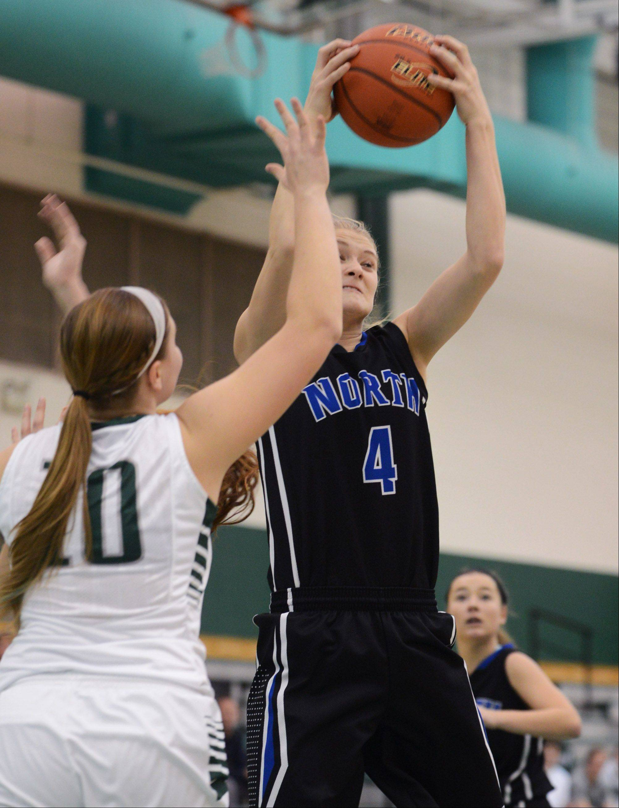 St. Charles North's Morgan Rosencrants (4) pulls down a rebound over Grayslake Central's Maddy Miller on Thursday night in Grayslake.
