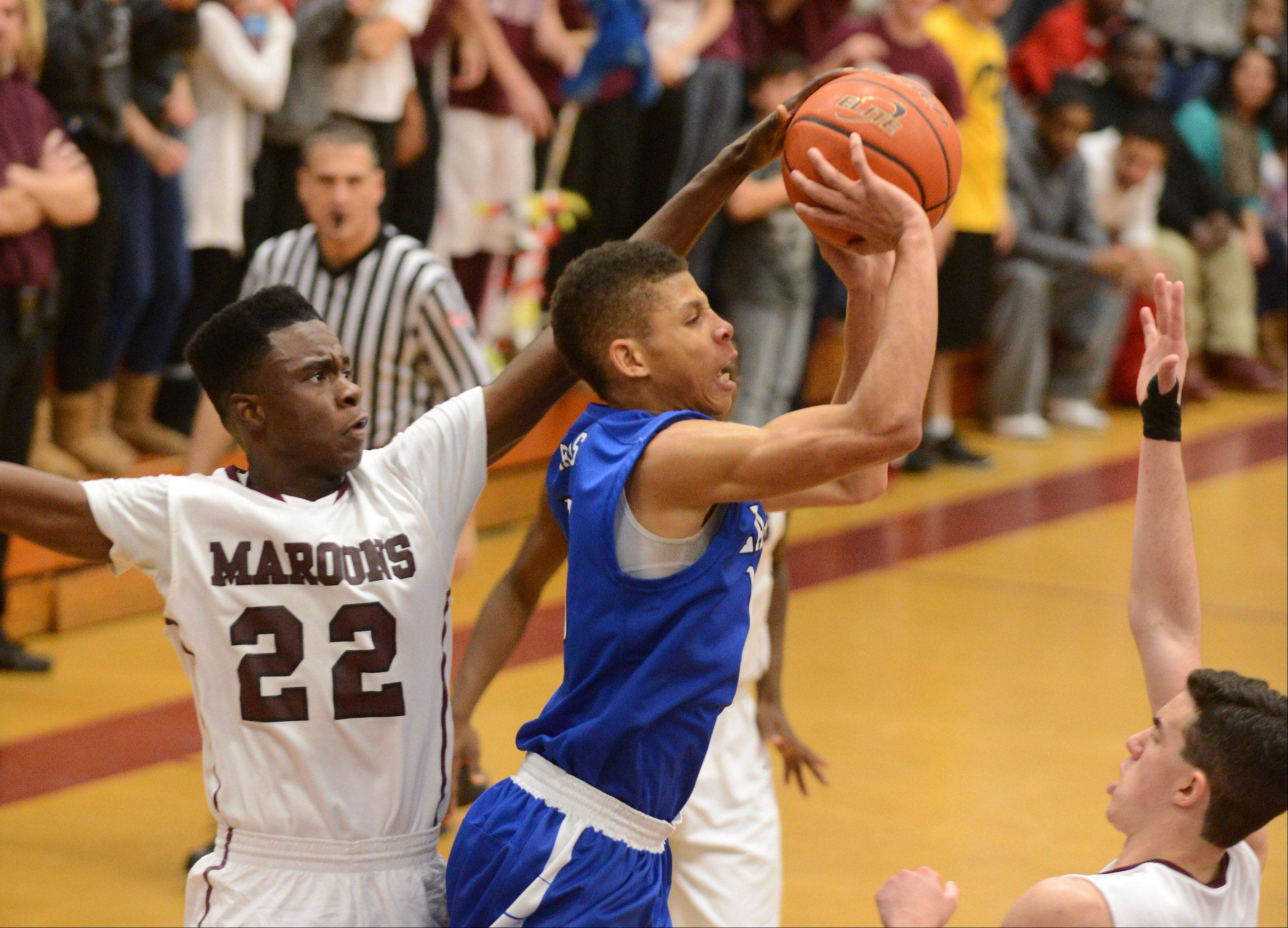 Larkin's Kendale McCullum puts up a shot between a pair of Elgin defenders, including Desmond Sanders.