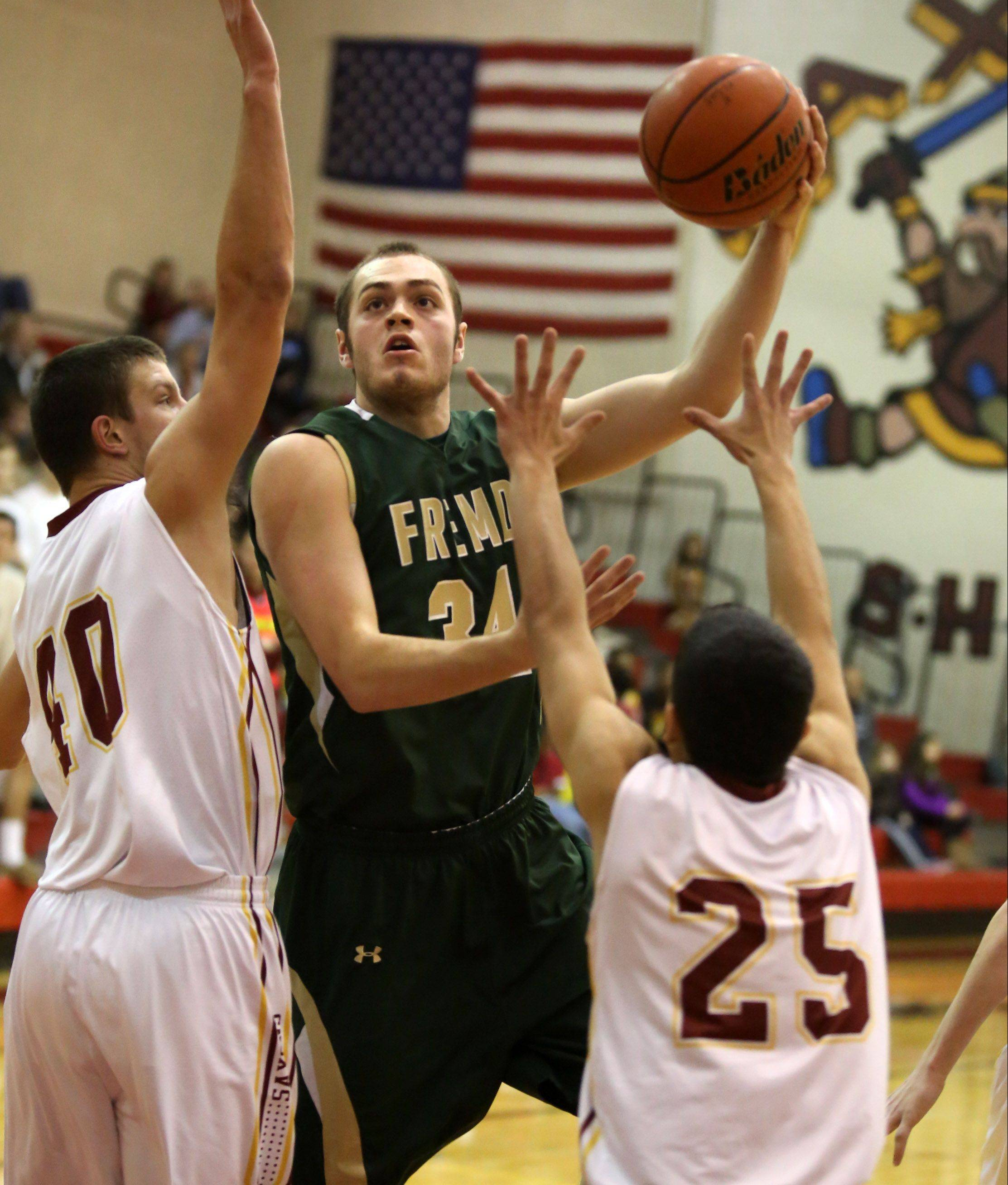 Fremd forward Ben Carlson splits two Schaumburg defenders including Demetrios Roumbos, right, on Friday in Schaumburg.